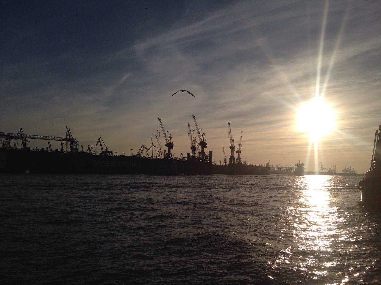 Silhouette Cranes Against Sky During Sunset At Harbor
