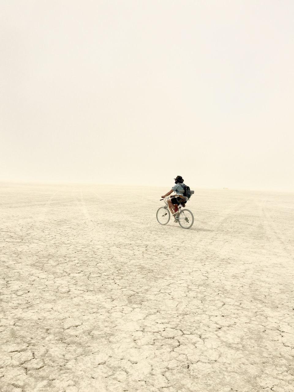 Full Length Of Man Riding Bicycle At Desert