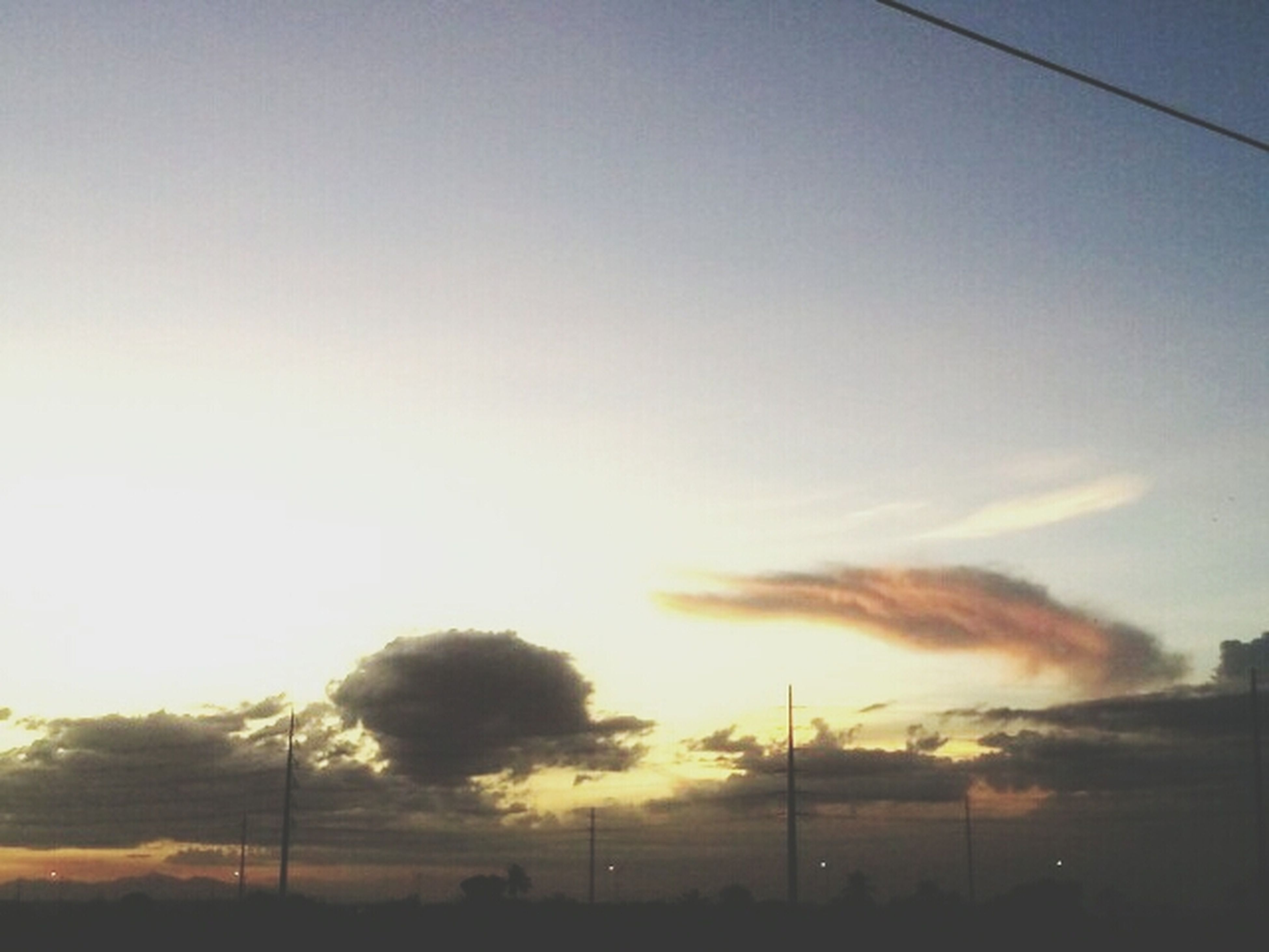 sunset, sky, silhouette, tranquility, tranquil scene, beauty in nature, electricity pylon, scenics, nature, low angle view, landscape, orange color, field, fuel and power generation, electricity, cloud - sky, street light, outdoors, power line, dusk
