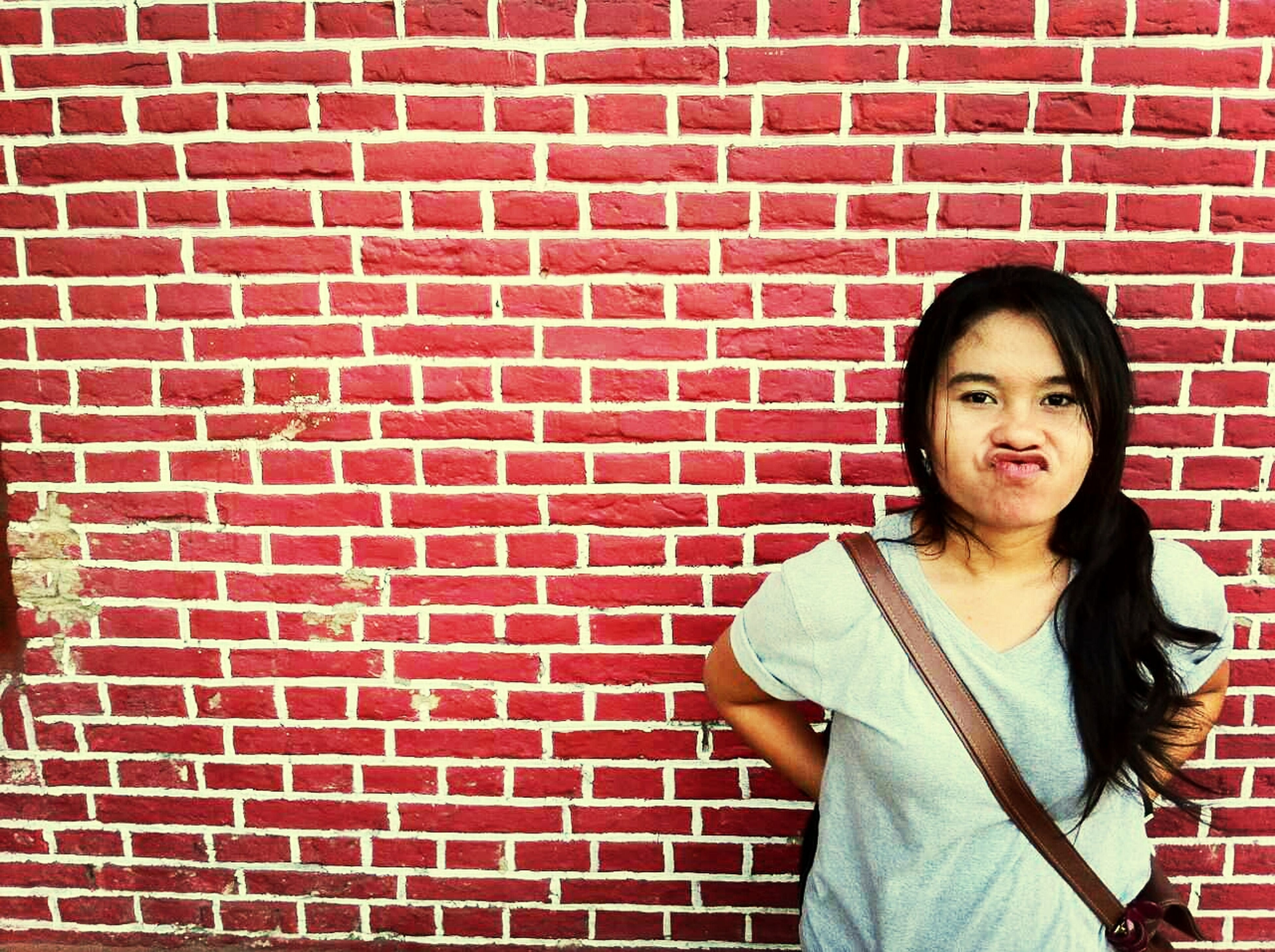 young adult, looking at camera, portrait, lifestyles, person, front view, young women, casual clothing, standing, leisure activity, brick wall, smiling, wall - building feature, red, happiness, waist up