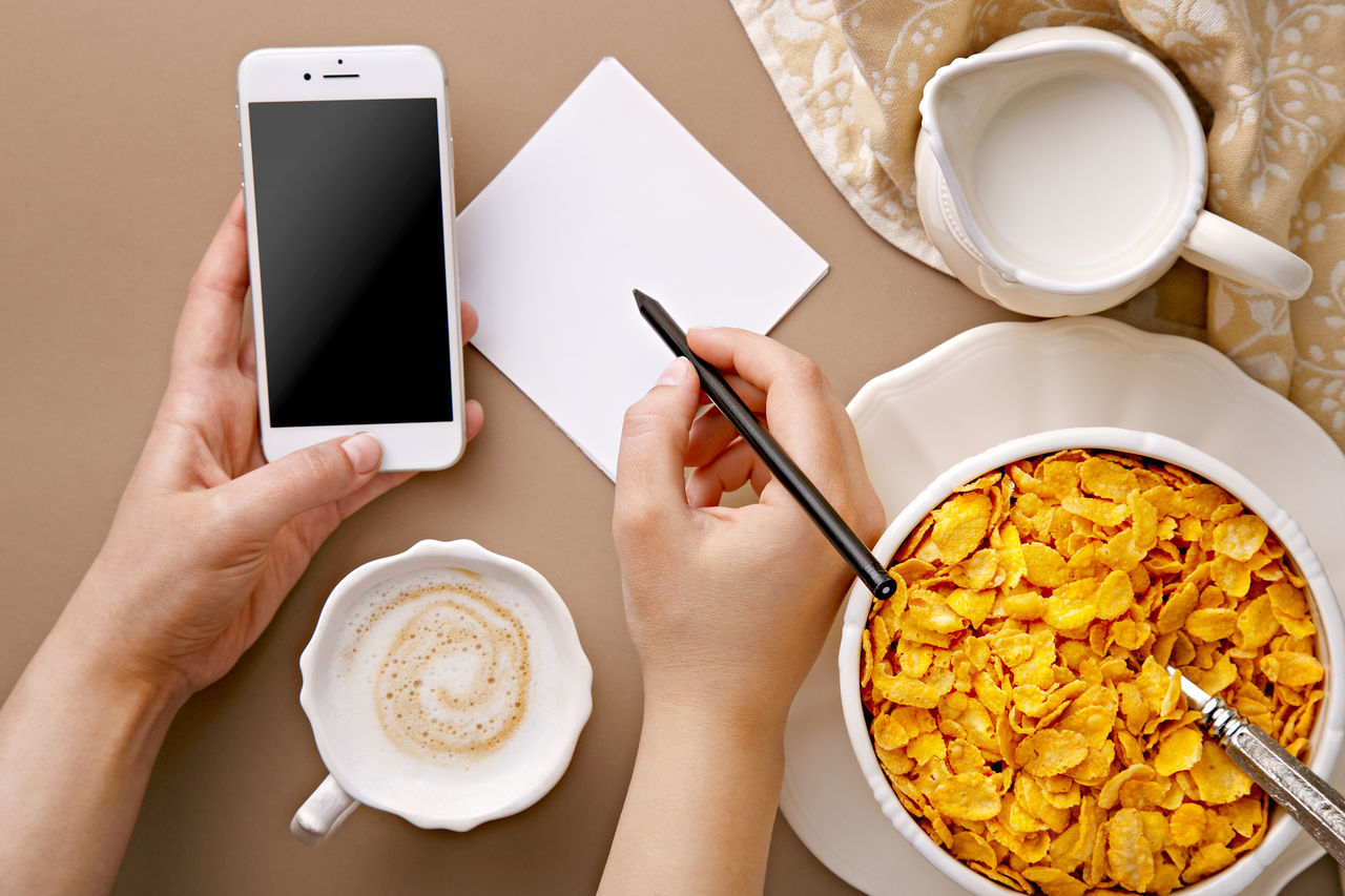 Cropped Hand Of Woman Holding Pen While Using Phone By Corn Flakes At Table
