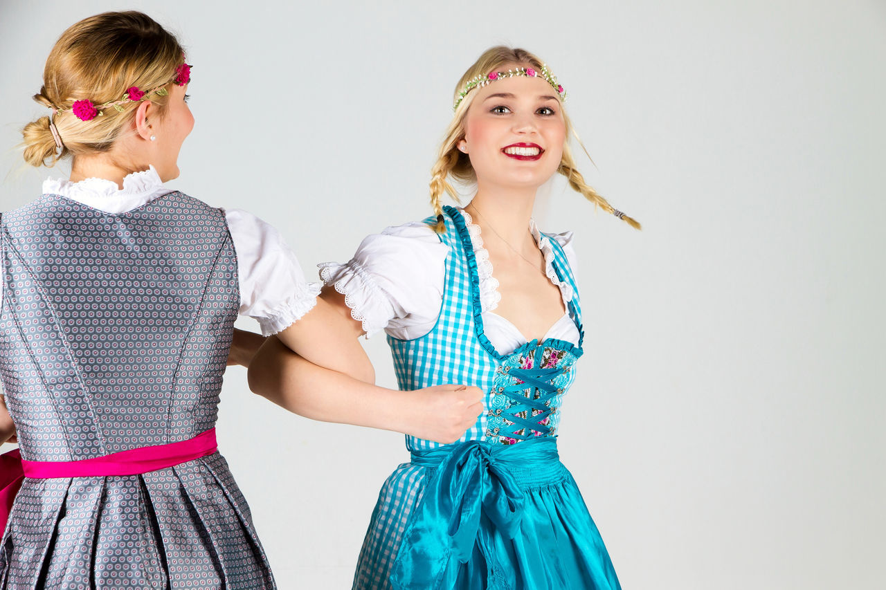 Two happy girls dancing in dirndl Bavaria Beautiful Beauty Blue Celebration Clothes Dance Dirndl Fashion Festival Fun Germany Girl Happiness Happy Munich Oktoberfest Portrait Smiling Together Traditional Two White Woman Young