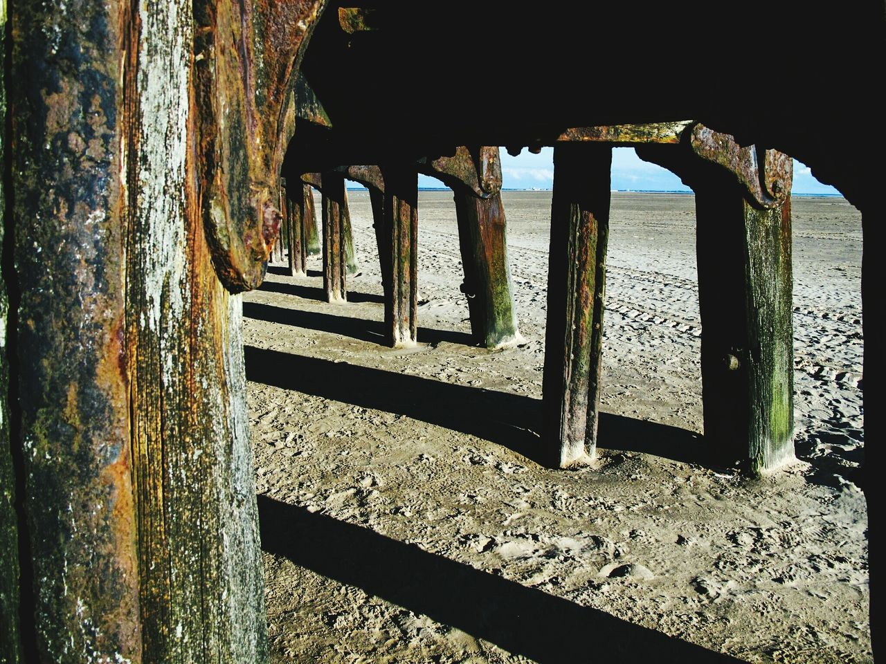 Underneath View Of Weathered Pier At Beach
