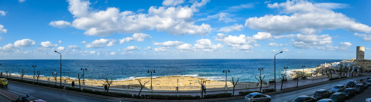 sea, sky, horizon over water, railing, water, cloud - sky, day, sunlight, transportation, outdoors, blue, nature, panoramic, scenics, architecture, built structure, beauty in nature, beach, city, road, no people, building exterior, cityscape, nautical vessel, tree
