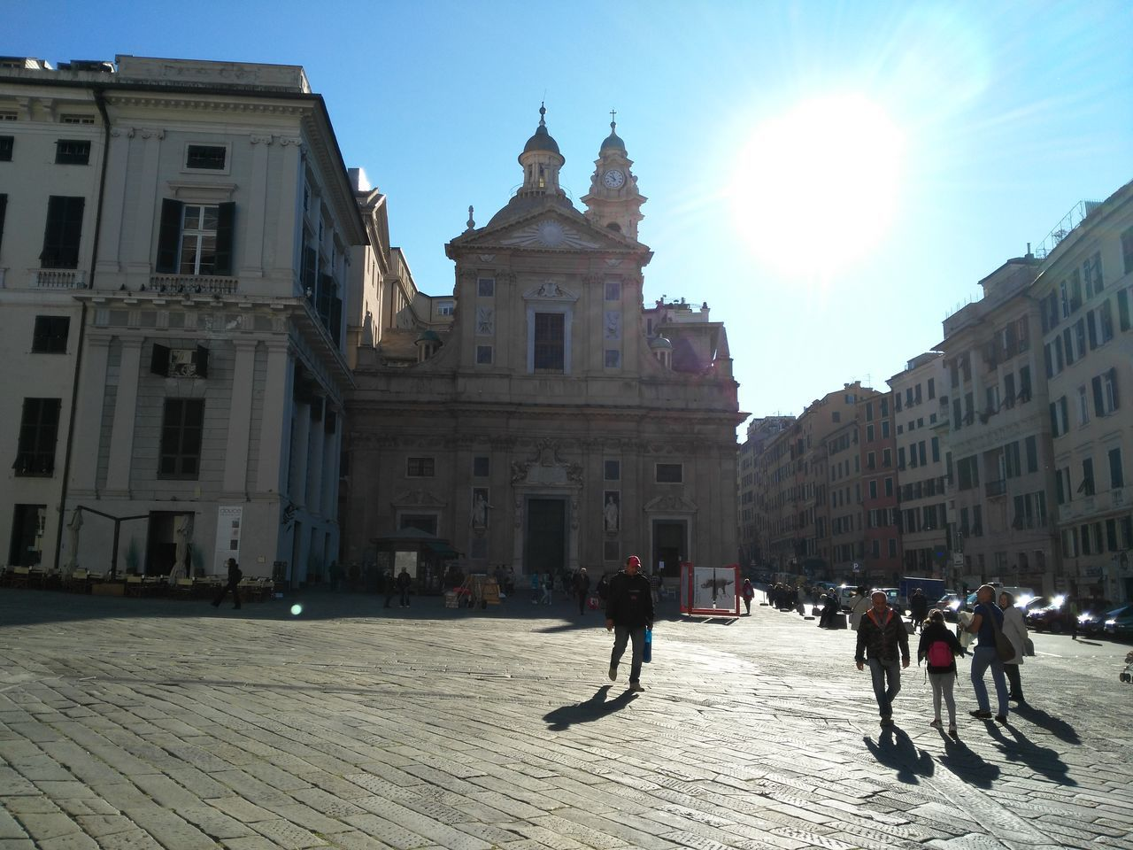 architecture, building exterior, built structure, sunlight, sky, real people, sun, outdoors, city, place of worship, spirituality, day, large group of people, travel destinations, men, people