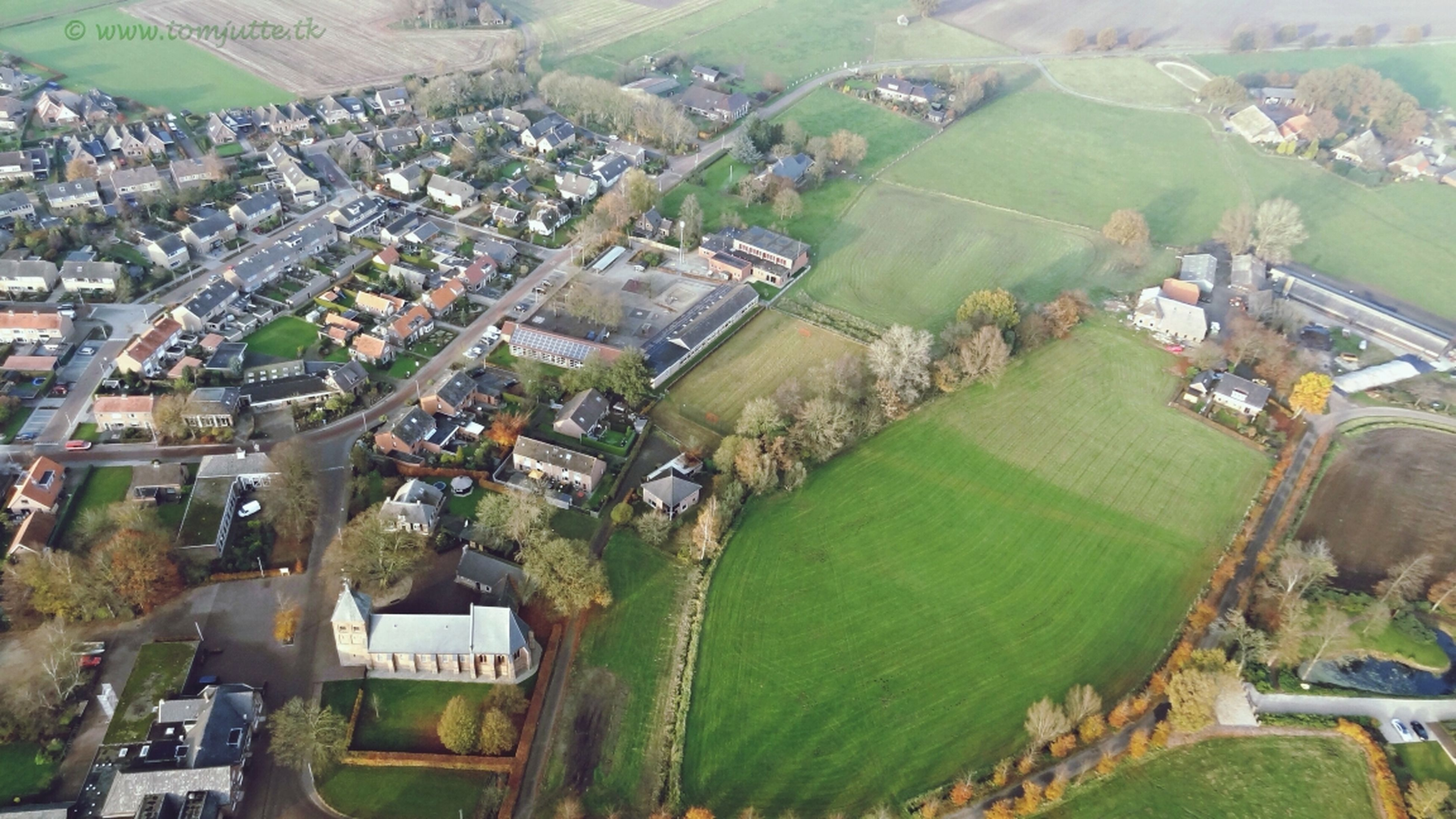 high angle view, landscape, building exterior, aerial view, built structure, architecture, agriculture, green color, cityscape, rural scene, farm, field, residential district, city, tree, crowded, house, nature, mountain, residential building