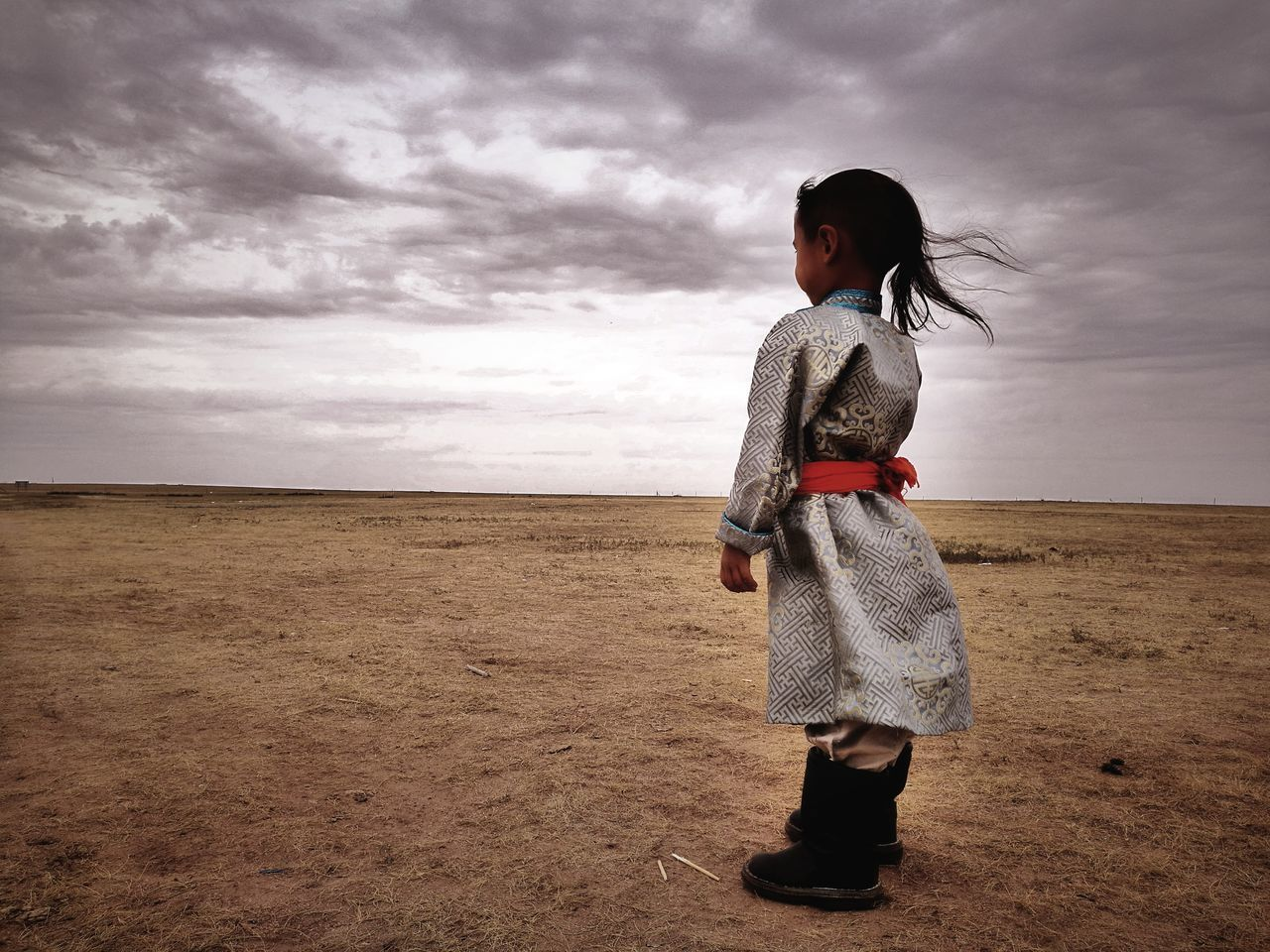 cloud - sky, sky, full length, one person, childhood, real people, standing, sand, outdoors, landscape, sea, field, nature, beach, horizon over land, day, lifestyles, girls, scenics, desert, beauty in nature, storm cloud, people