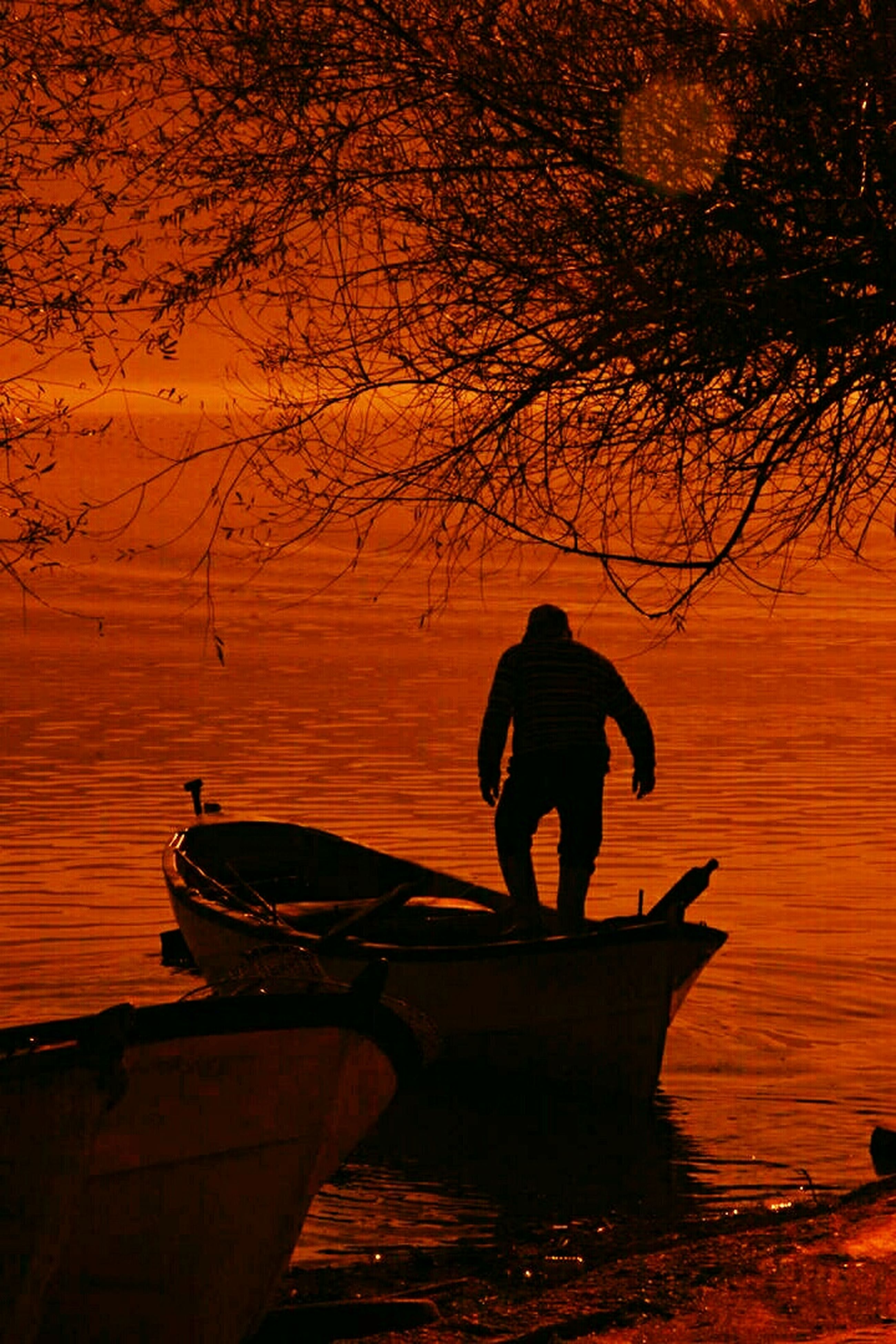 sunset, water, silhouette, orange color, full length, lifestyles, leisure activity, men, tranquility, rear view, reflection, nature, tranquil scene, standing, beauty in nature, transportation, scenics, person
