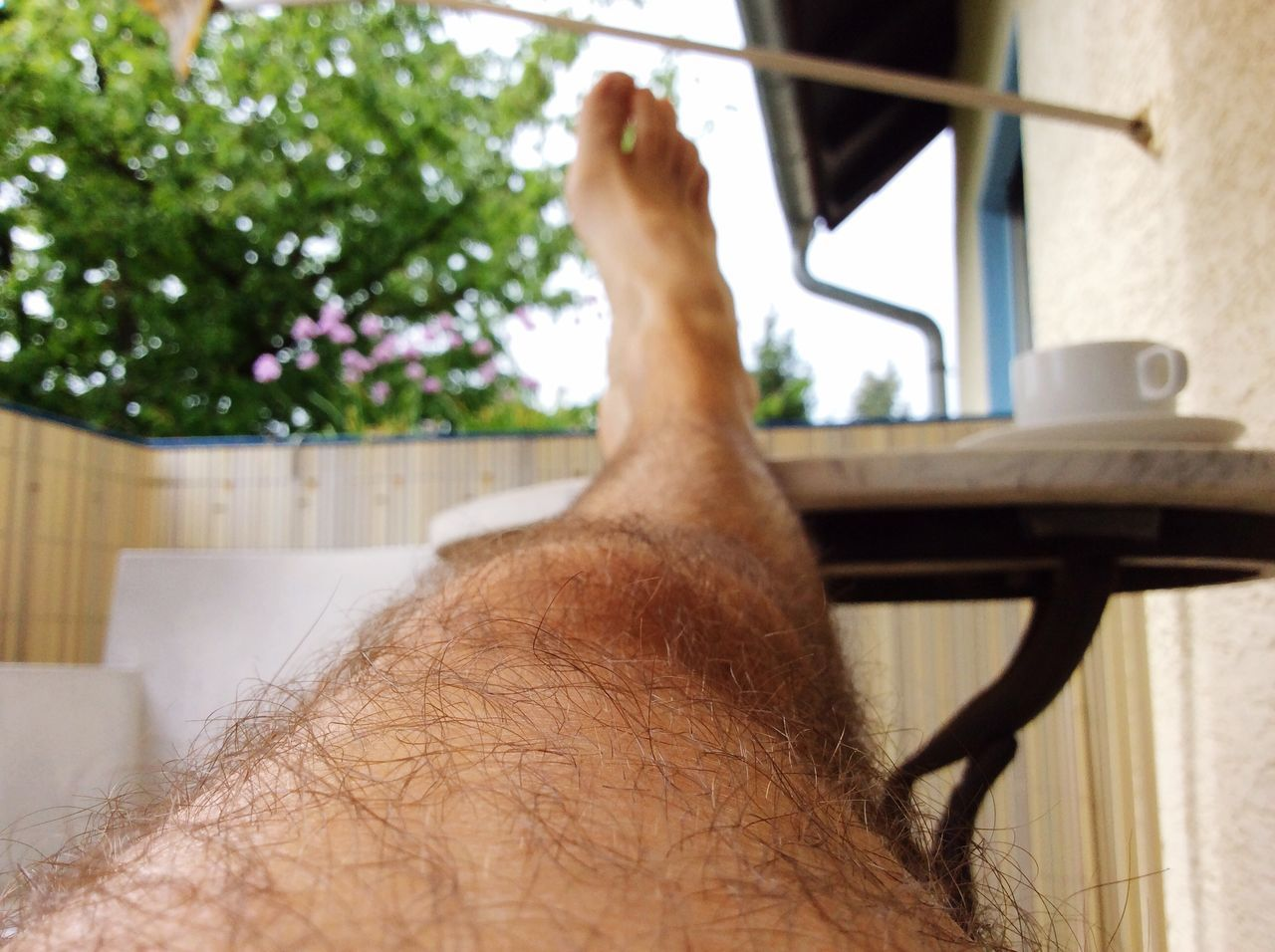 Cropped Leg On Table In Balcony