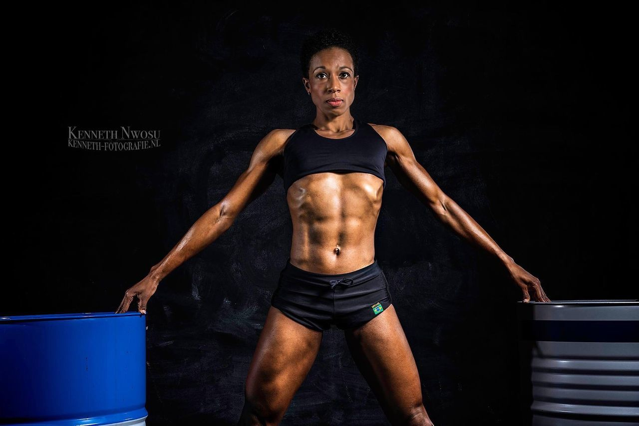 front view, lifestyles, looking at camera, exercising, standing, portrait, real people, young adult, one person, black background, adult, athlete, people, adults only, day
