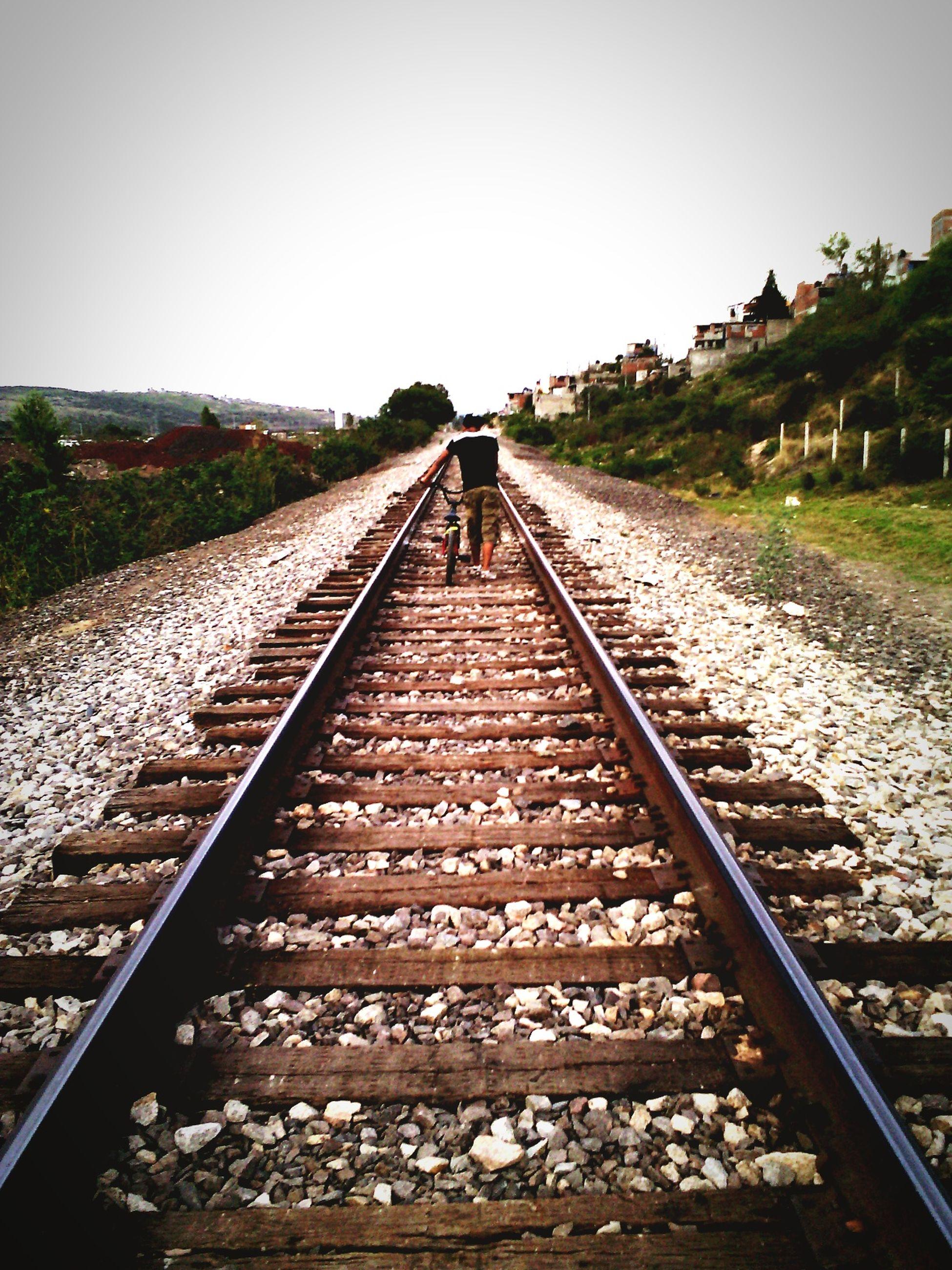 railroad track, rail transportation, transportation, clear sky, diminishing perspective, the way forward, vanishing point, railway track, public transportation, travel, sky, railroad station platform, day, railroad station, gravel, tree, outdoors, straight