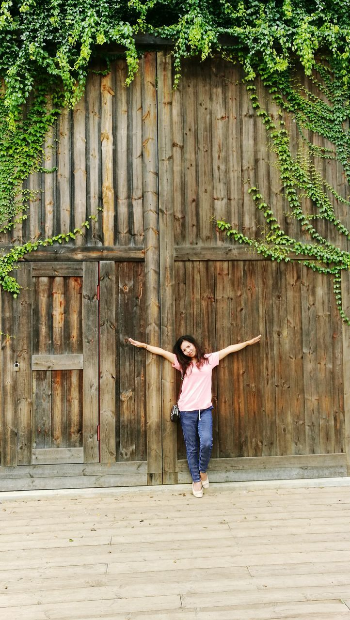 Woman With Arms Outstretched Leaning On Wooden Entrance Gate