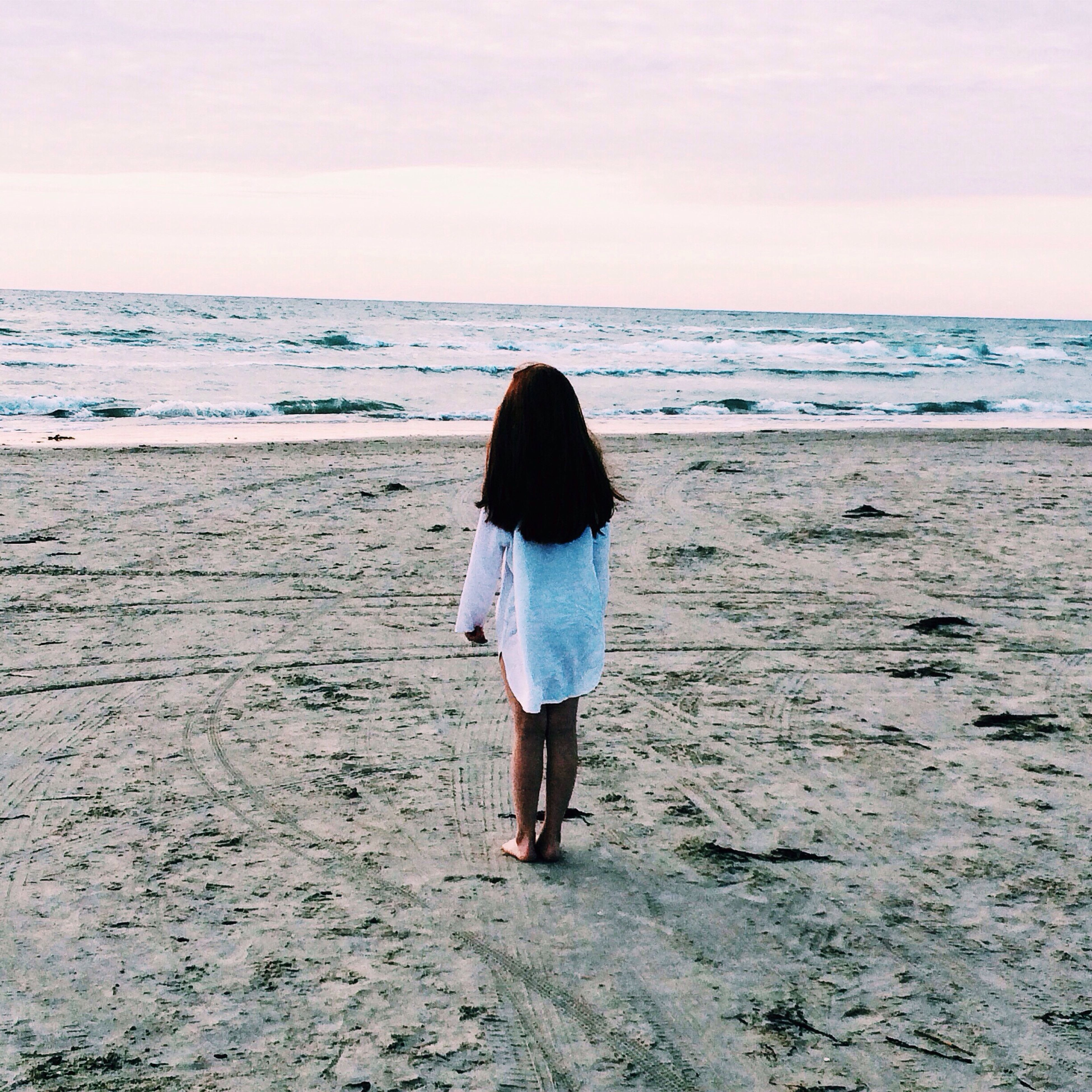 beach, sea, rear view, full length, horizon over water, standing, shore, lifestyles, sky, sand, tranquility, leisure activity, water, tranquil scene, walking, casual clothing, beauty in nature, person
