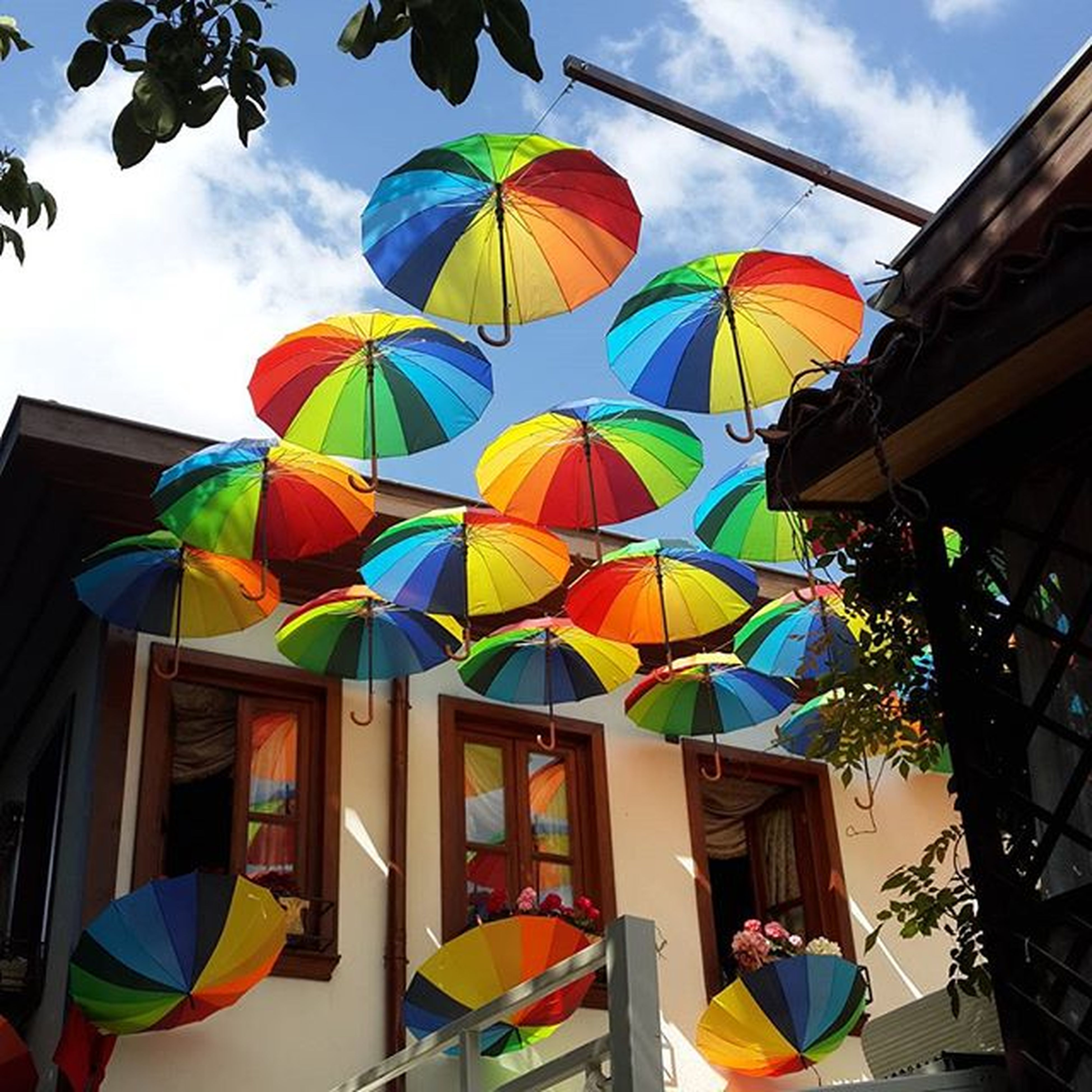 multi colored, low angle view, architecture, sky, built structure, building exterior, colorful, blue, hanging, cloud, cloud - sky, in a row, variation, house, day, yellow, no people, outdoors, window, umbrella