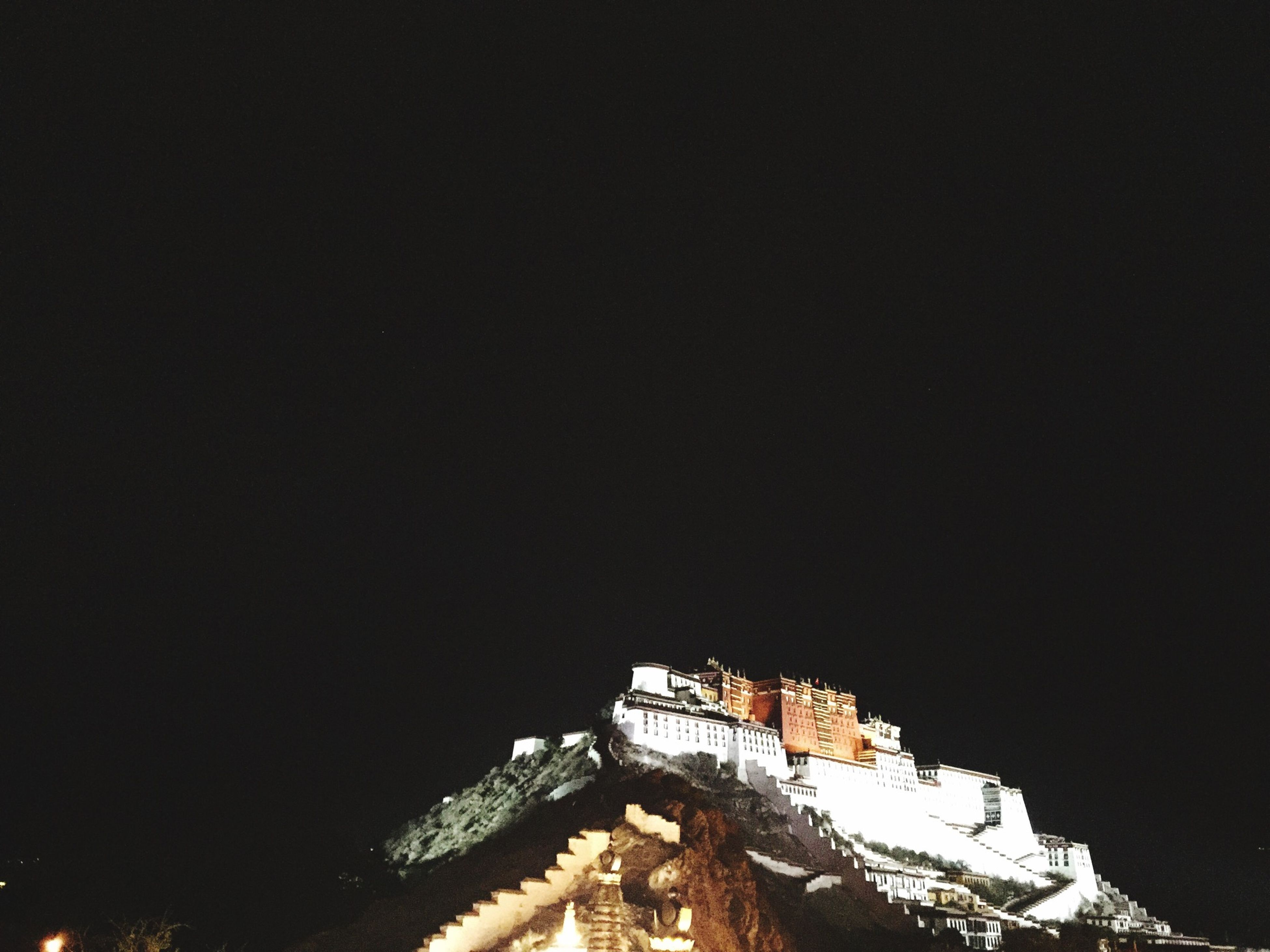 architecture, built structure, copy space, clear sky, building exterior, night, low angle view, outdoors, no people, high angle view, illuminated, sky, nature, house, building, high section, dusk, residential structure, travel destinations, mountain