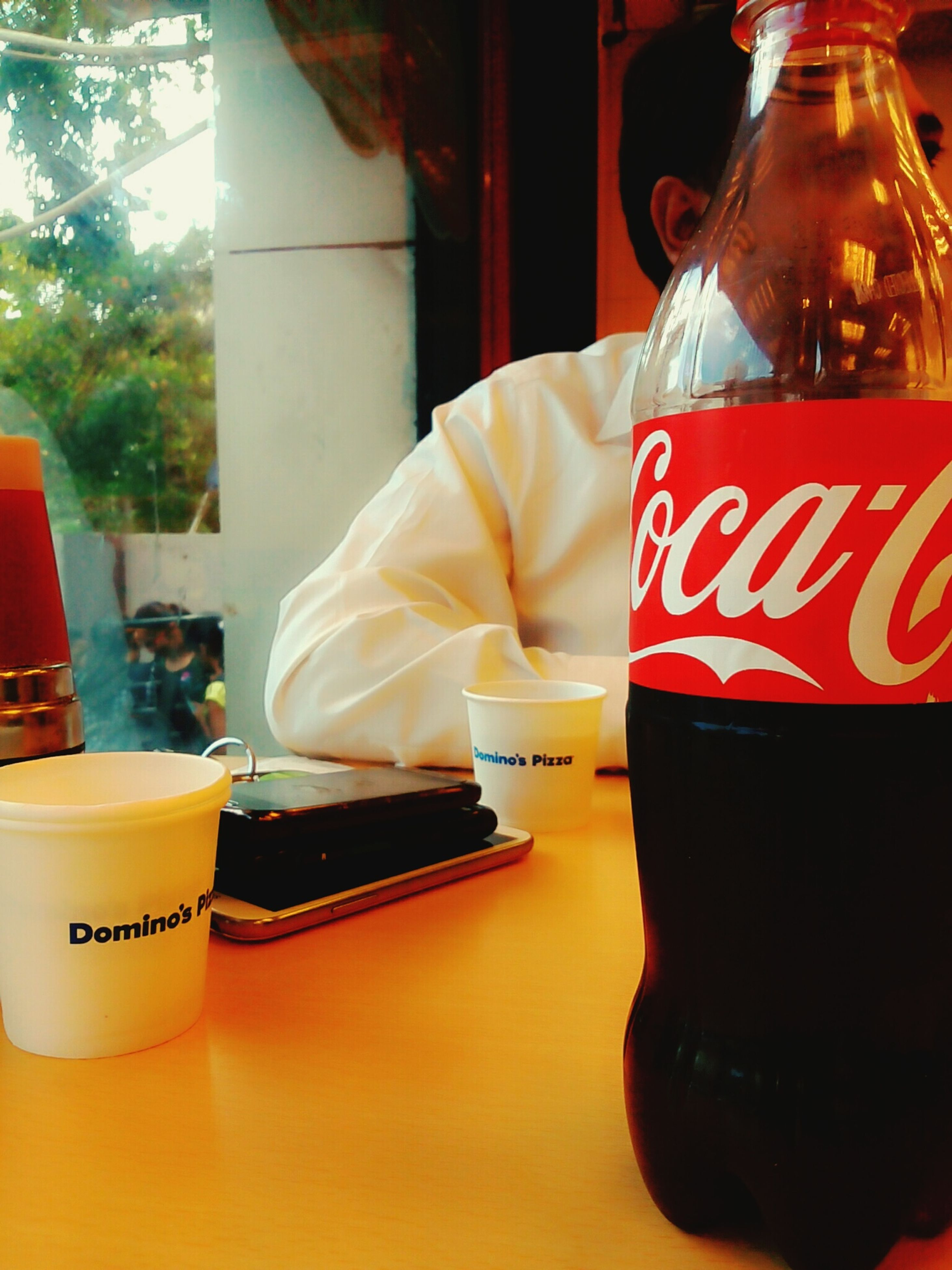 text, drink, communication, indoors, western script, food and drink, table, red, focus on foreground, close-up, restaurant, still life, non-western script, incidental people, refreshment, day, glass - material, men, cafe
