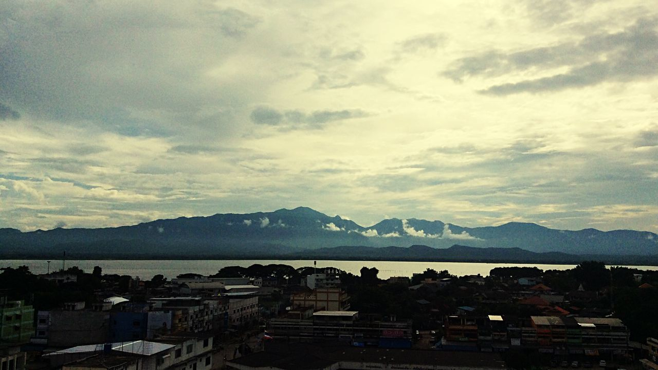 mountain, sky, building exterior, architecture, built structure, mountain range, cloud - sky, high angle view, no people, outdoors, town, water, day, scenics, beauty in nature, nature, cityscape, city, sea