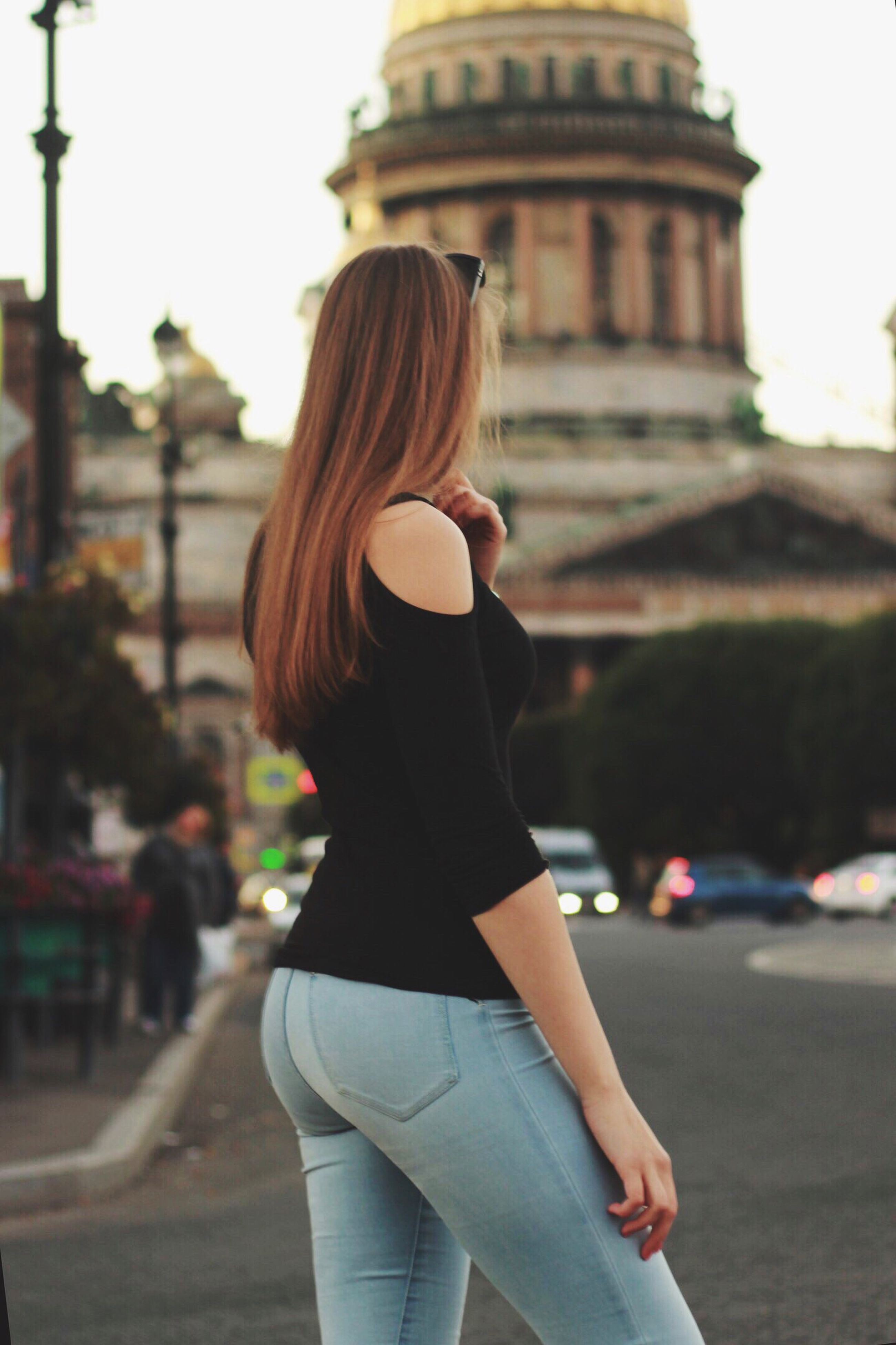 standing, focus on foreground, leisure activity, three quarter length, lifestyles, long hair, road, architecture, city, casual clothing, blond hair, city life, building exterior, person, young adult, outdoors, holding, day