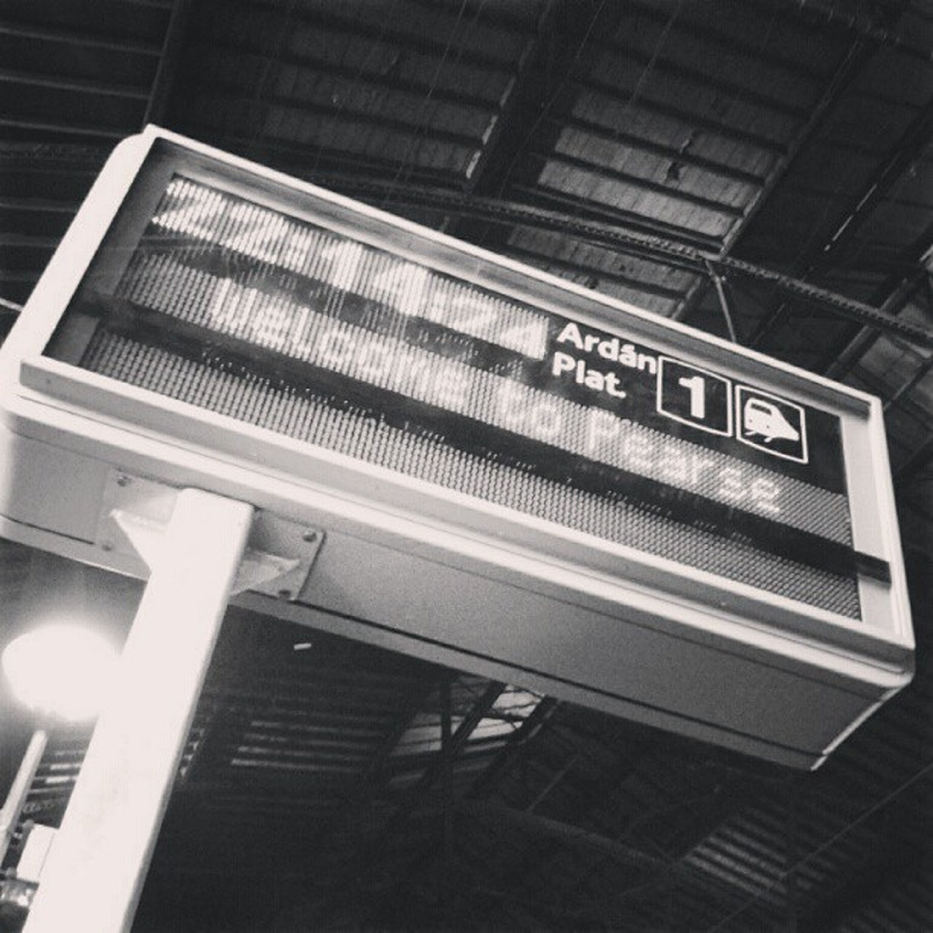 architecture, built structure, text, low angle view, western script, communication, building exterior, illuminated, indoors, railroad station, building, information sign, modern, ceiling, subway station, sign, city, information, lighting equipment, non-western script