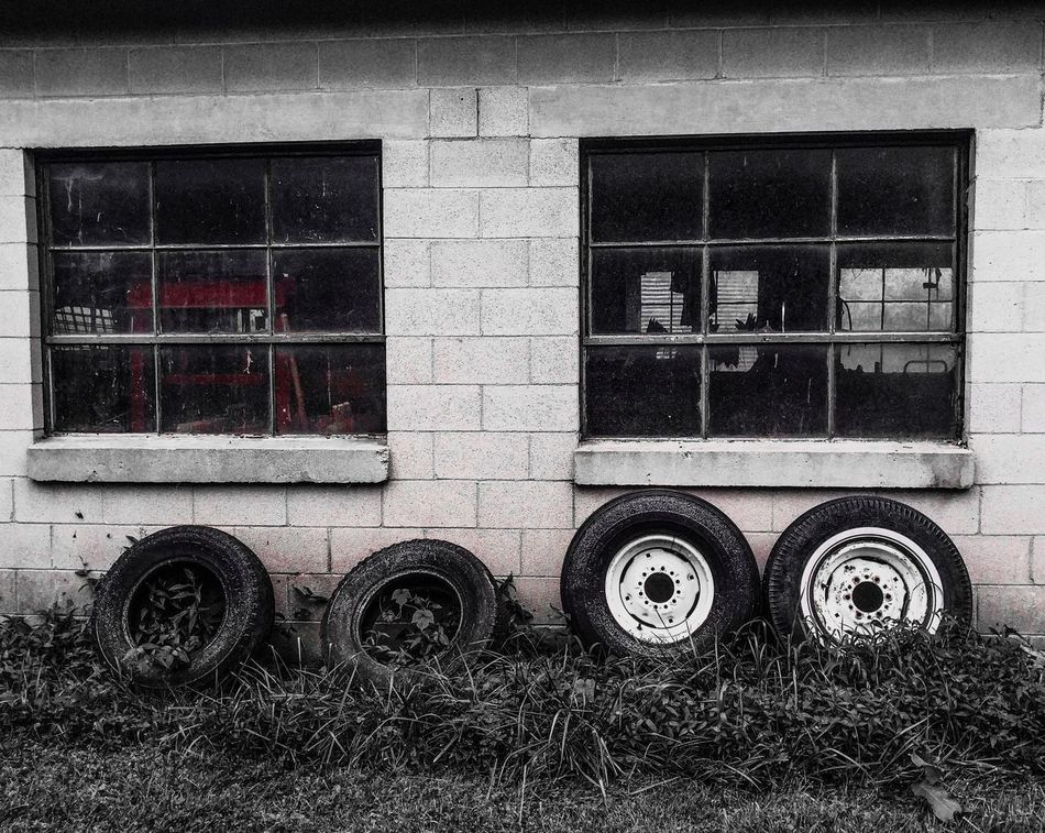 Four on the floor leaned up against a wall Window Day Building Exterior Outdoors No People Architecture Close-up Tires Garage Glass Farm Grass