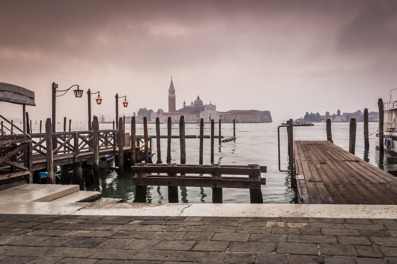 Pier On Venetian Lagoon Against Cloudy Sky