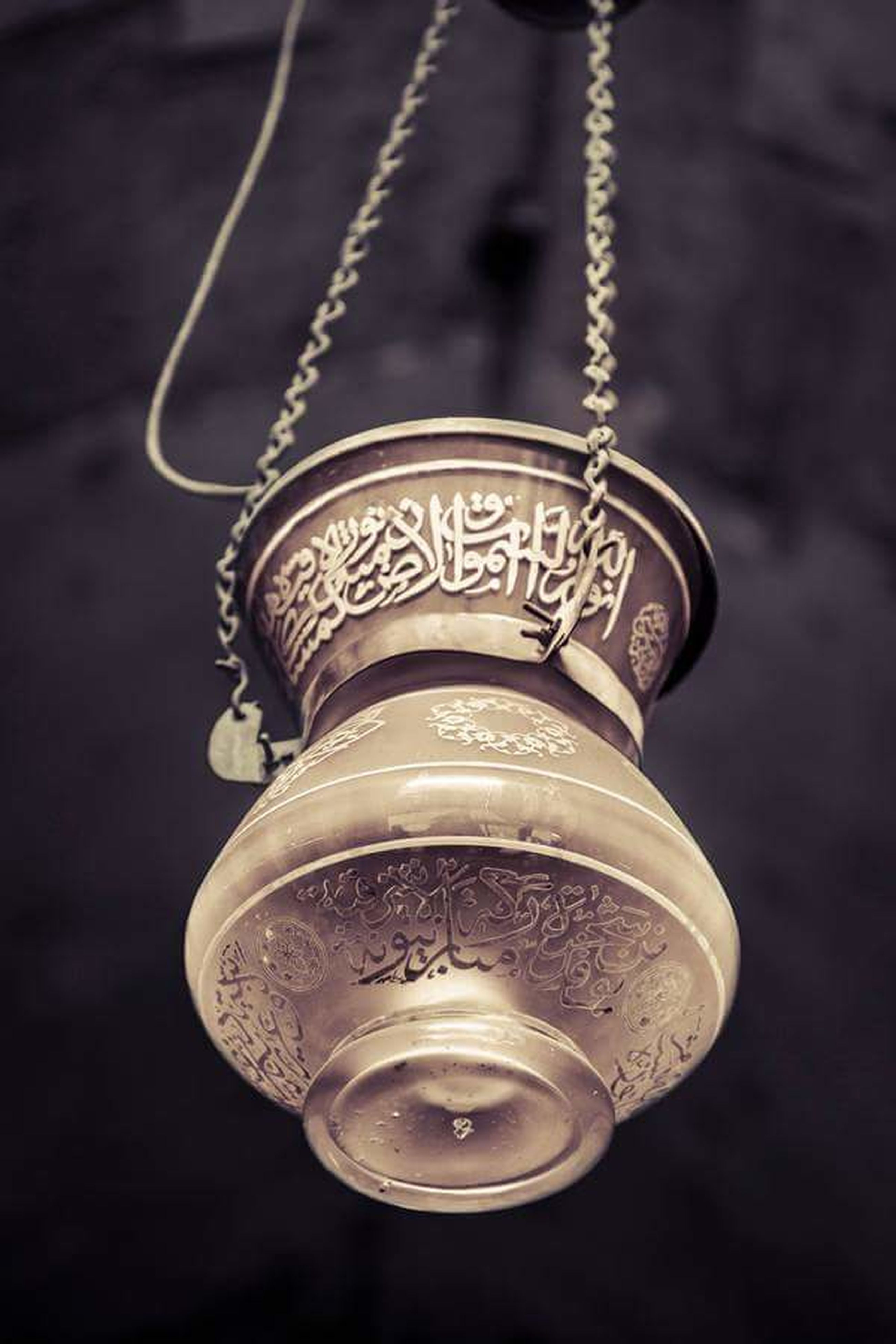 close-up, indoors, metal, single object, focus on foreground, still life, metallic, old-fashioned, hanging, lighting equipment, no people, electricity, selective focus, light bulb, man made object, table, text, old, technology, retro styled