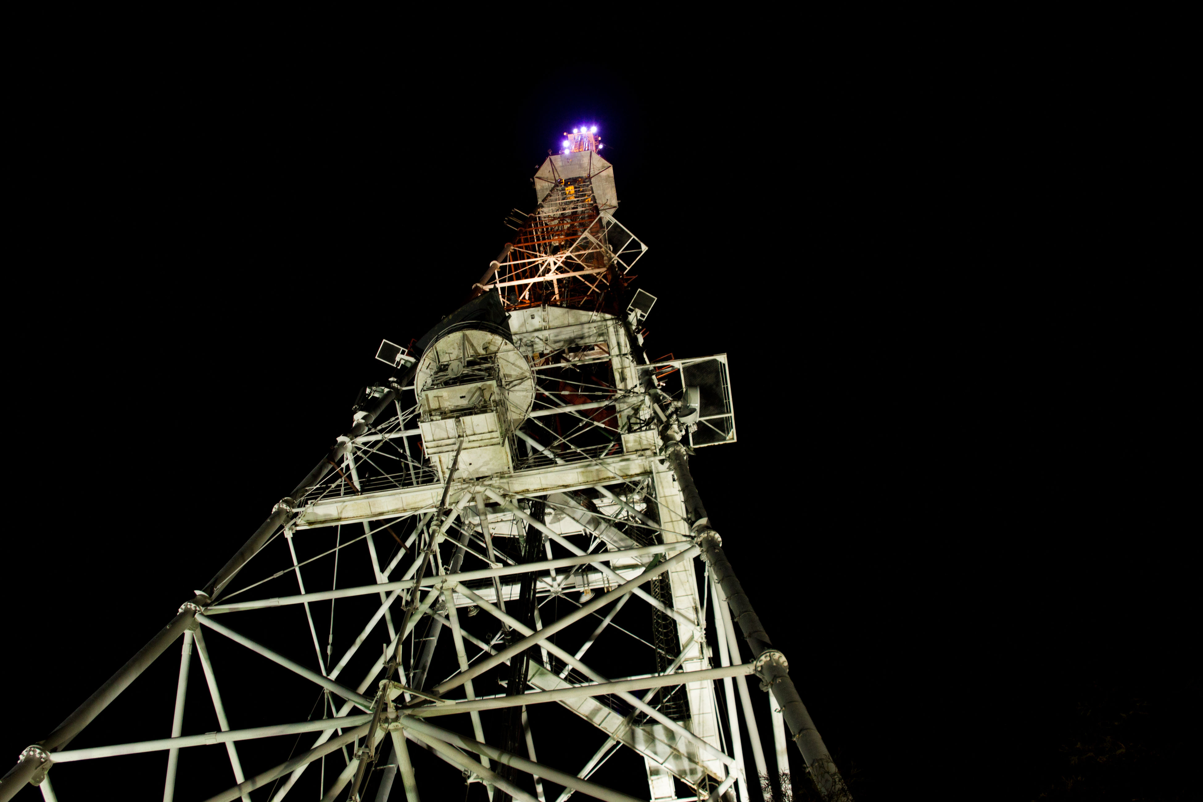 night, architecture, built structure, illuminated, low angle view, no people, black background, outdoors, clear sky, building exterior, technology, sky, drilling rig