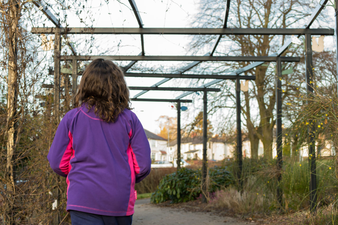 Girl Walking Wooden Structure Wood - Material Outdoors Outside From Behind Trees Houses One Person Colour Image Standing Horizontal Human Hair Park - Man Made Space Real People One Child Child People Watching Childhood Nature Day Built Structure Grass Leaves