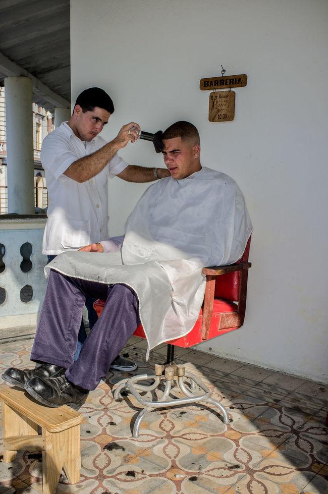 Man having his hair cut in a sidewalk barber shop in Pinar del Rio, Cuba. Barber Shop Cuba Cutting Hair Hairdresser Street Streetside Tourism Travel Travel Destinations Street Photographer - 2016 EyeEm Awards
