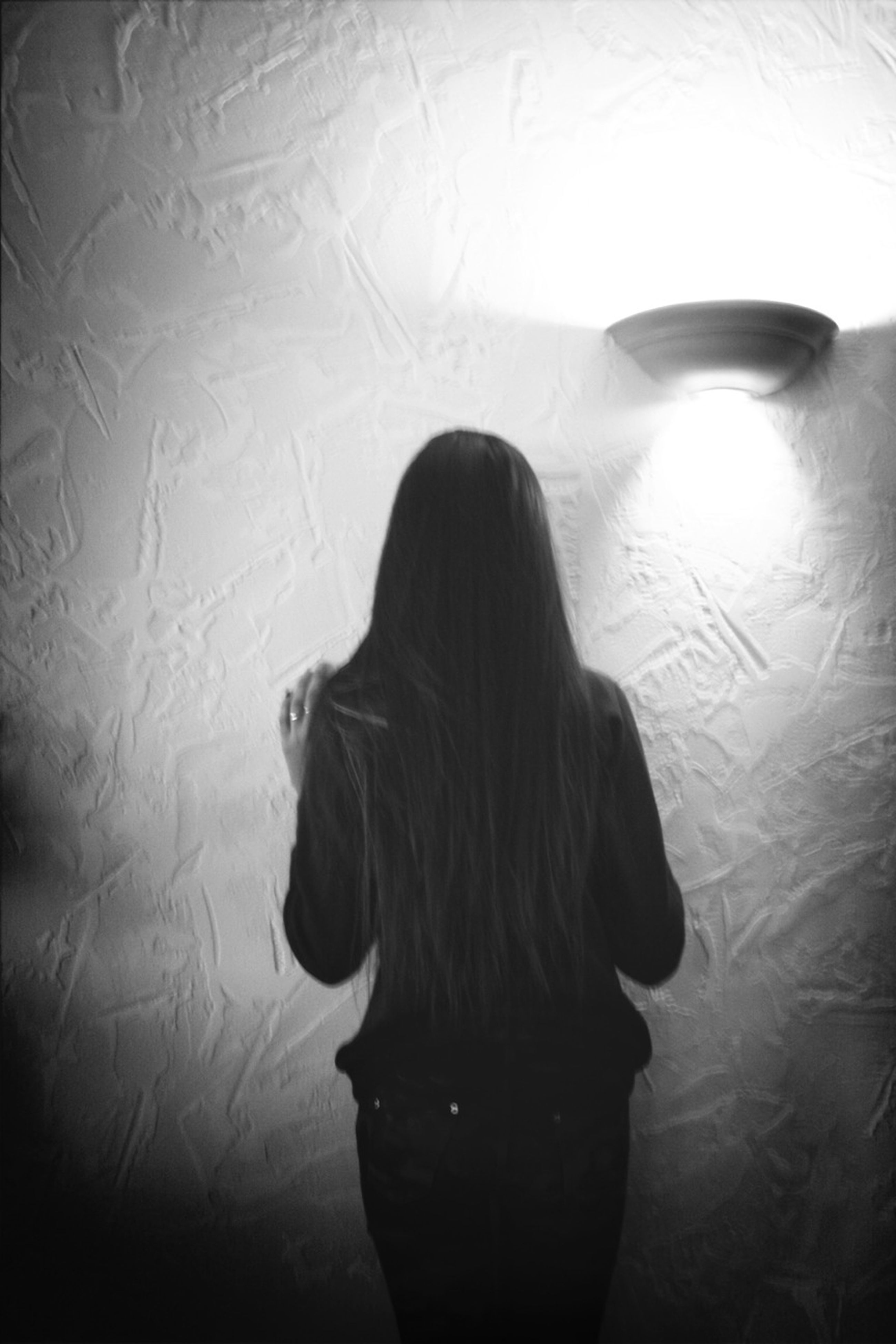 indoors, long hair, lifestyles, rear view, young women, headshot, young adult, leisure activity, waist up, standing, person, illuminated, front view, wall - building feature, three quarter length, silhouette, home interior