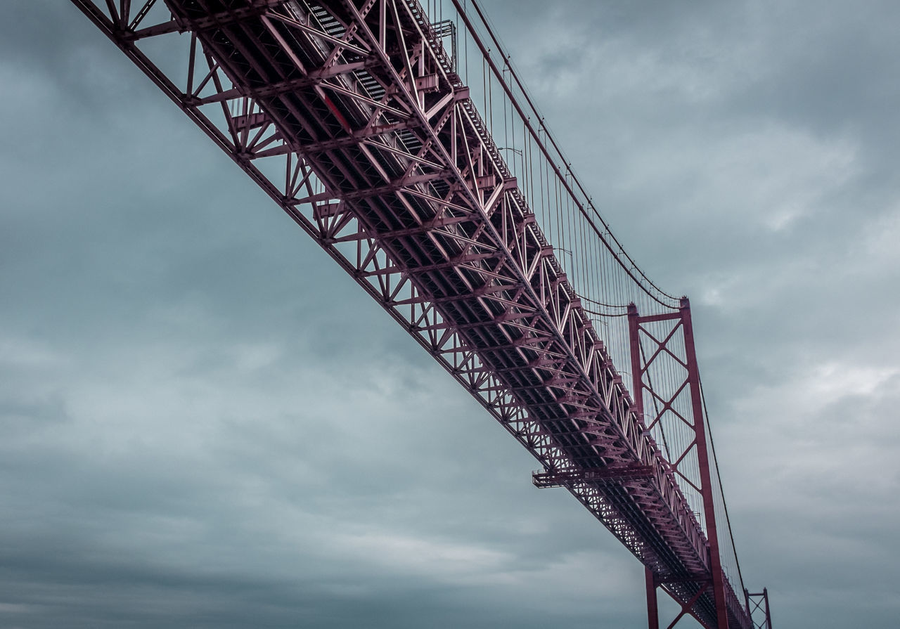 Low Angle View Of 25 De Abril Bridge Against Cloudy Sky