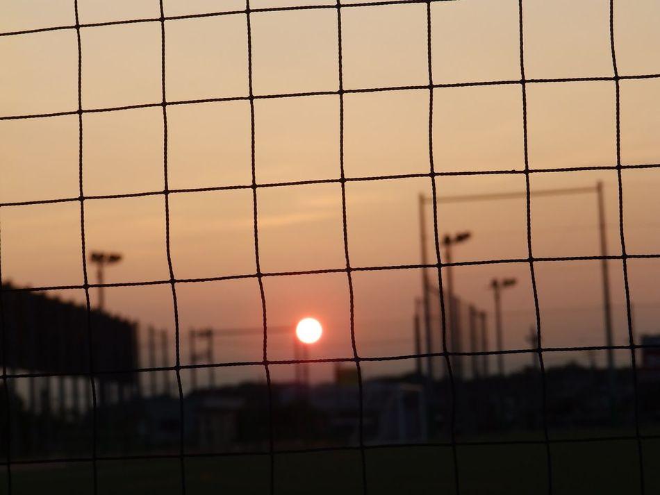 帰り道..。SUNDOWN.. visible through the school tennis and soccer ground. | Sunset Sundown Twilightscapes Silhouette Silouette & Sky Sunset_collection Sunset Silhouettes Olympus Olympusinspired Olympusphotography NoEditNoFilter Full Frame From My Point Of View EyeEmNewHere Eyeemgallery EyeEm Best Shots - Sunsets + Sunrise No People 夕焼けハンター 帰り道 帰り道シリーズ 夕焼け。。。何で寂しいんだろう… 夕日♡ 夕日が綺麗だー! Adapted To The City