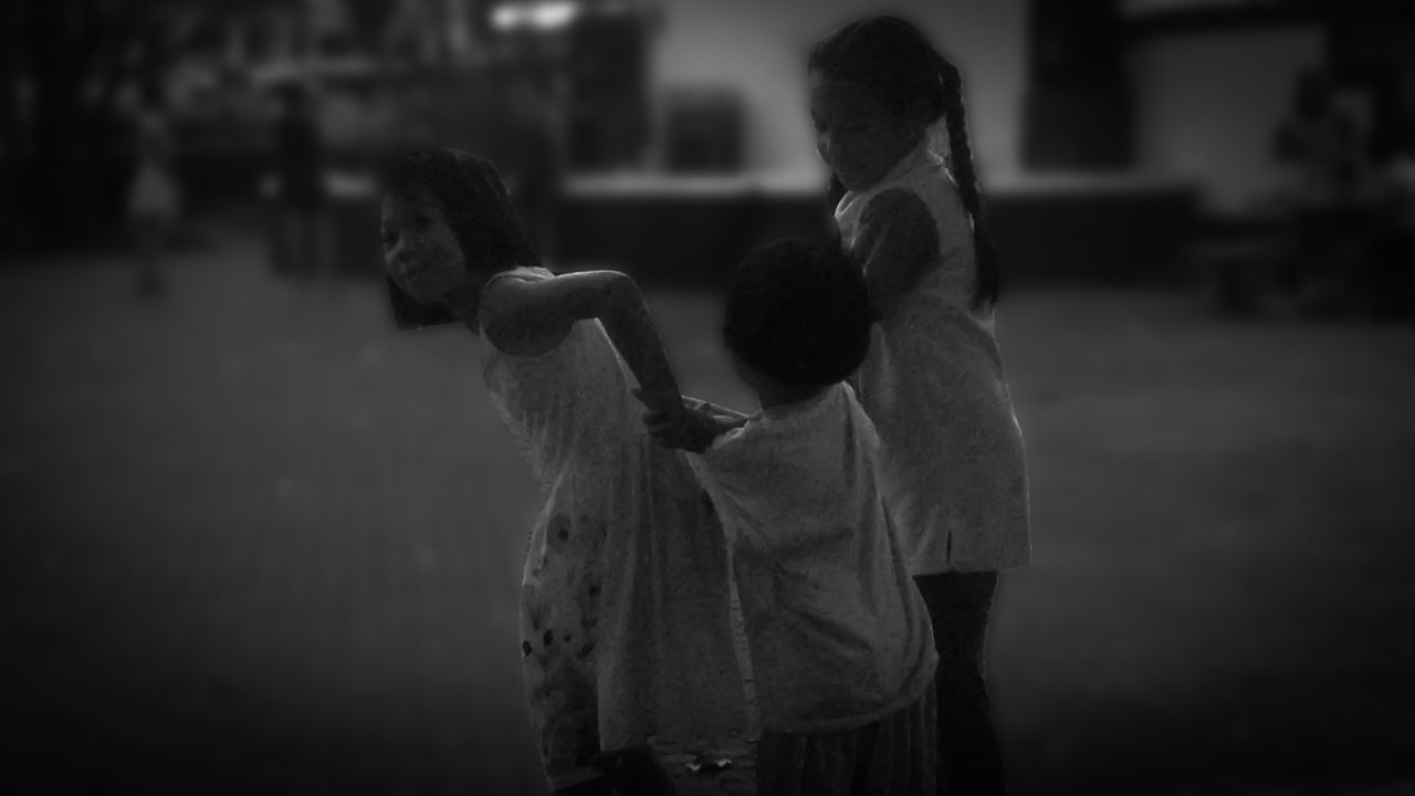 focus on foreground, rear view, childhood, real people, lifestyles, two people, standing, boys, outdoors, togetherness, men, night, friendship, people