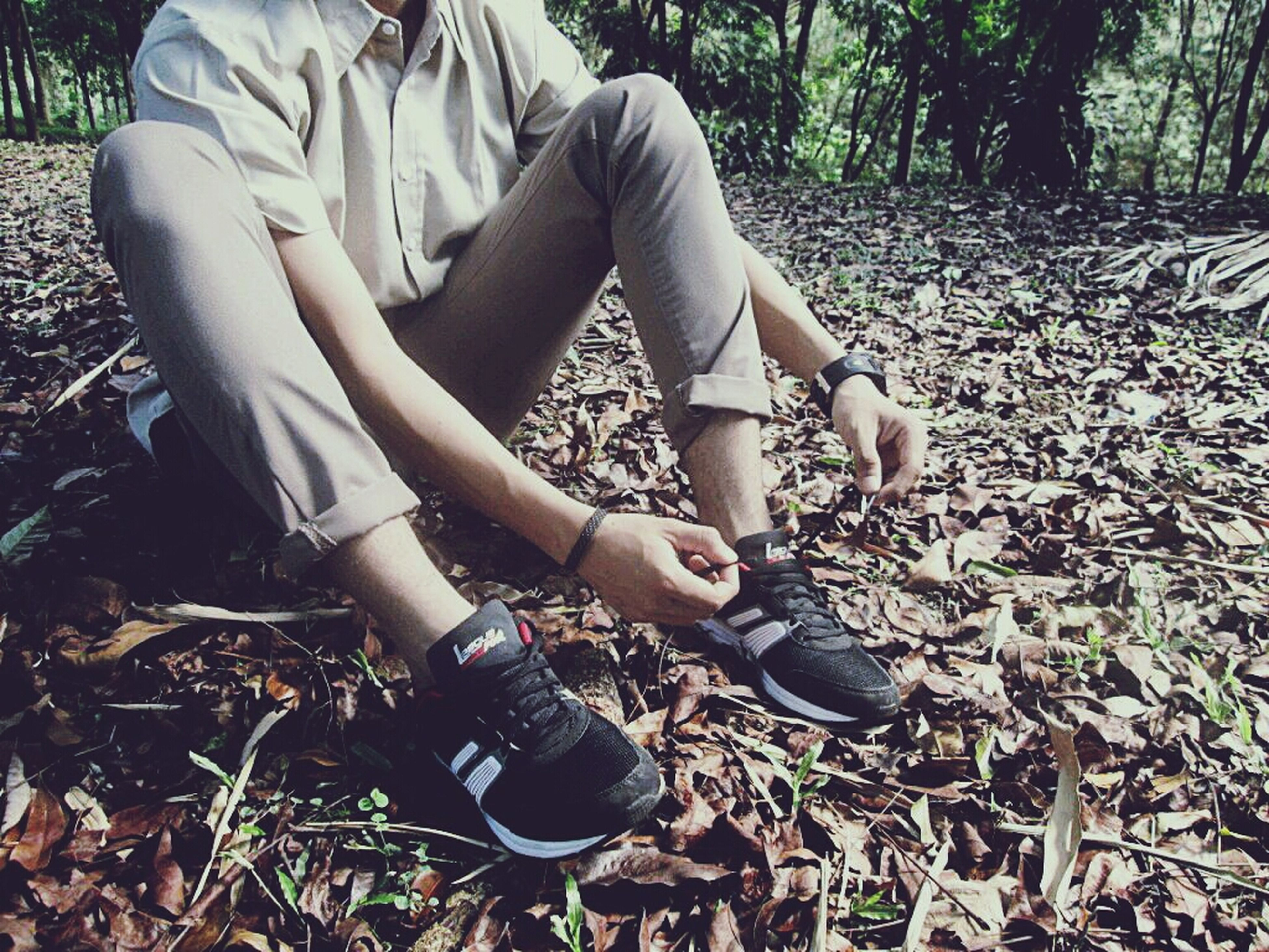 lifestyles, leisure activity, field, casual clothing, full length, childhood, outdoors, grass, day, sitting, holding, shoe, high angle view, nature, growth, forest, tree, plant