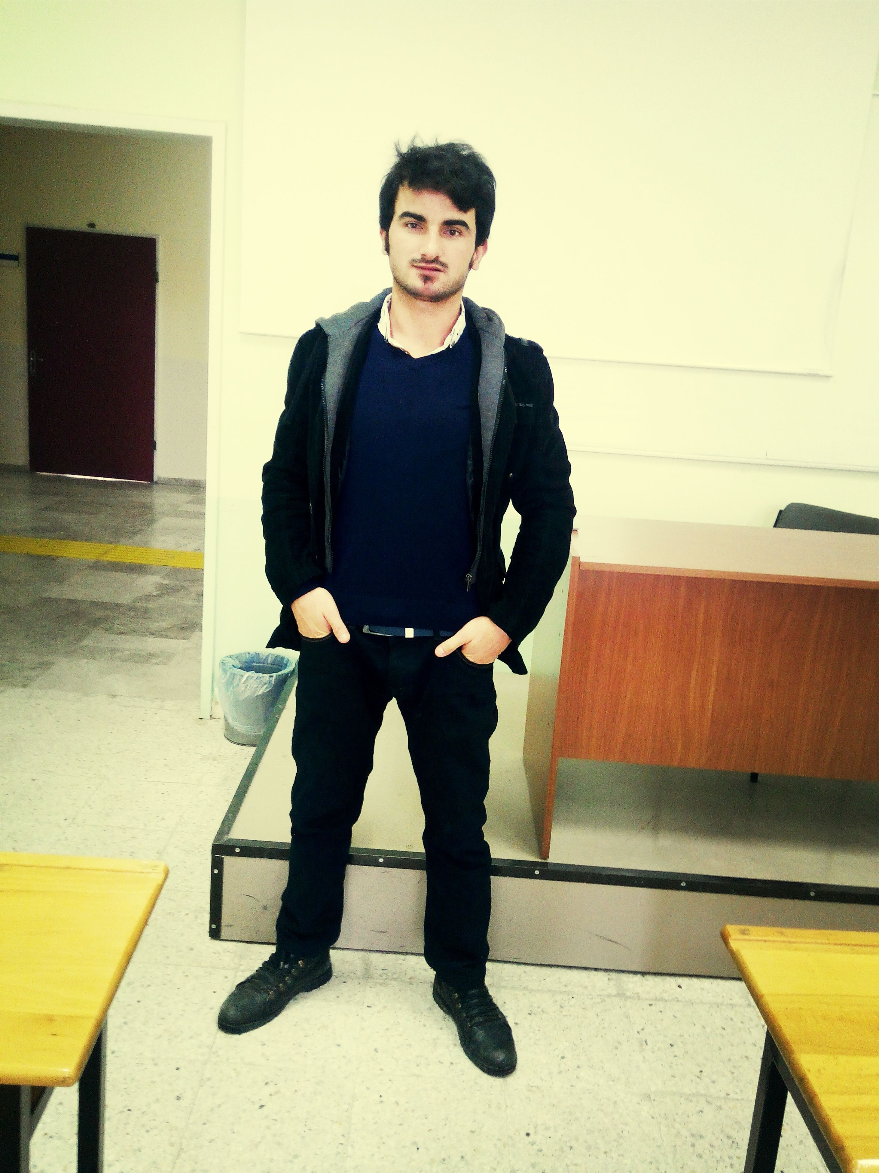 casual clothing, looking at camera, front view, portrait, standing, young adult, person, full length, lifestyles, young men, built structure, architecture, smiling, indoors, leisure activity, three quarter length, wall - building feature, sitting