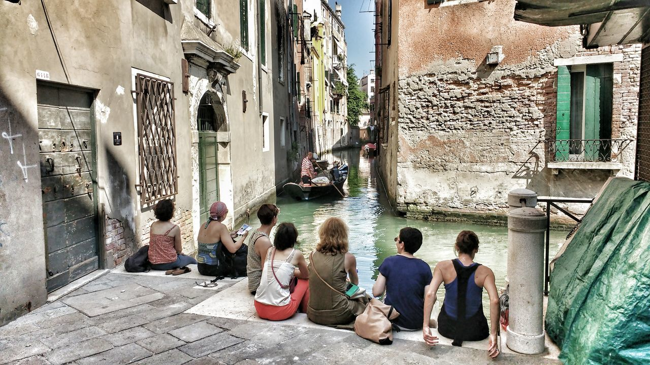 architecture, building exterior, built structure, sitting, real people, water, day, men, outdoors, medium group of people, women, lifestyles, city, adult, people, adults only