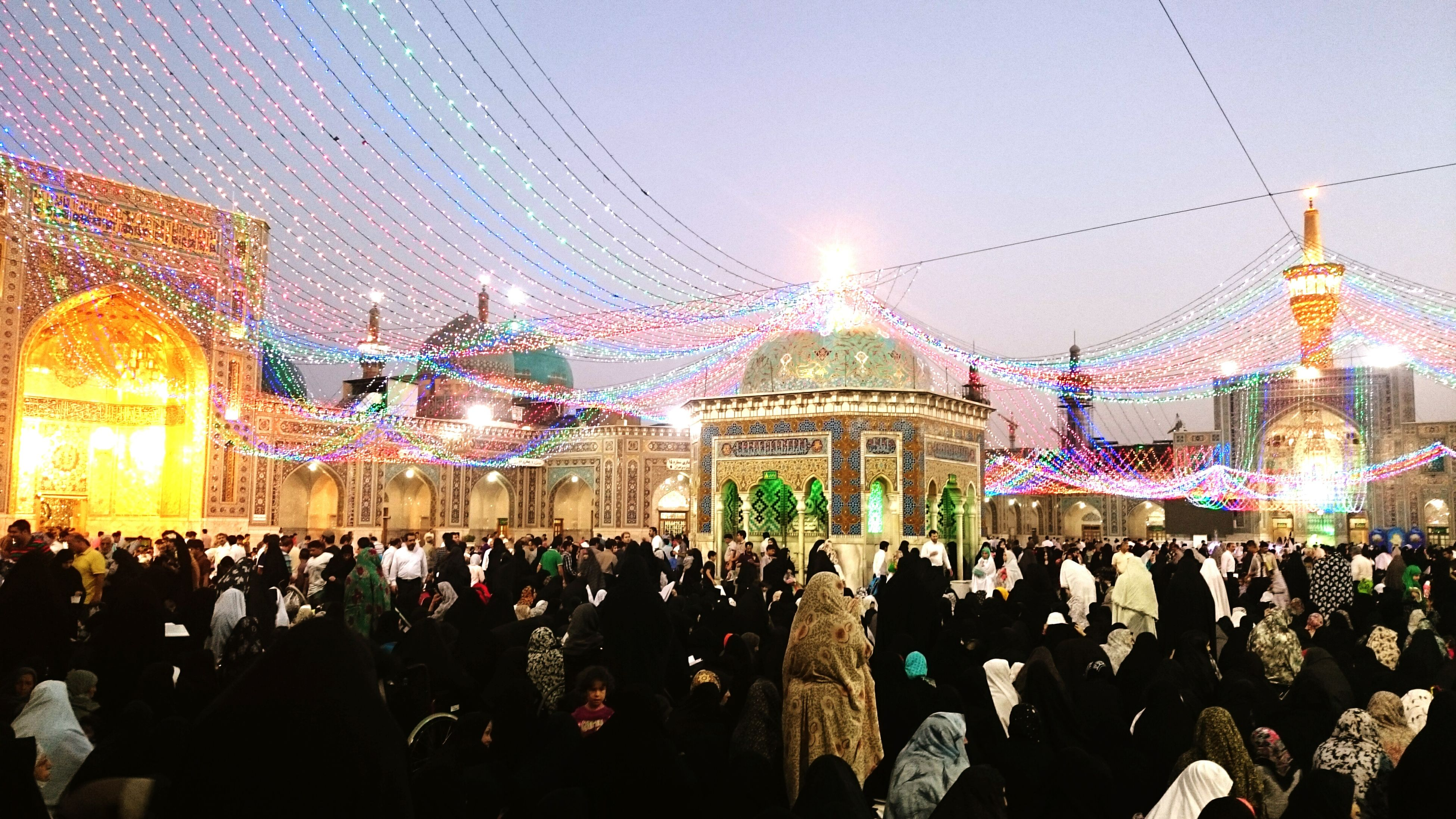 large group of people, crowd, illuminated, architecture, person, built structure, men, lifestyles, building exterior, celebration, leisure activity, lighting equipment, night, religion, mixed age range, sky, decoration, travel destinations, spirituality