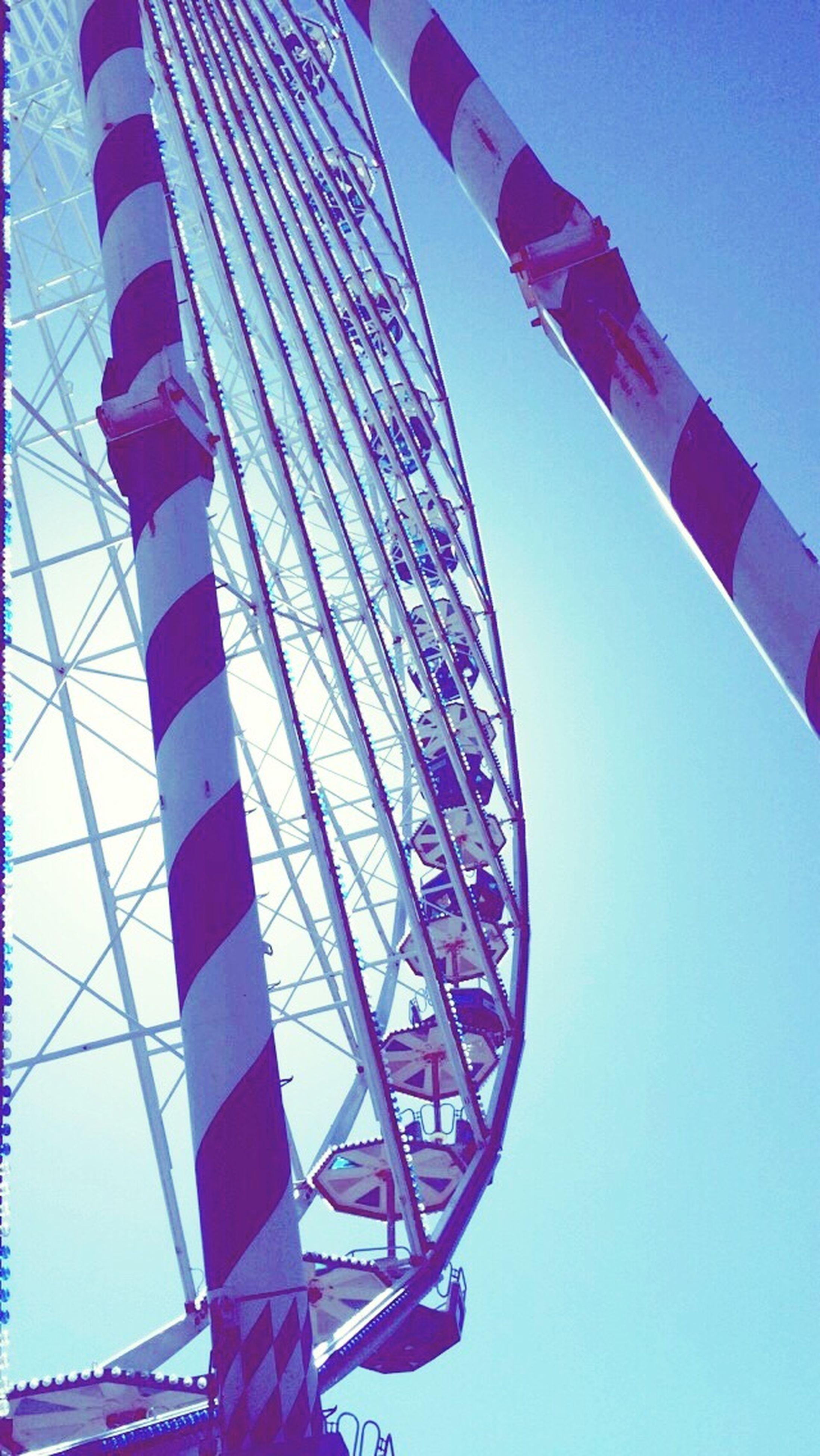 low angle view, blue, clear sky, multi colored, built structure, architecture, sky, amusement park, ferris wheel, circle, arts culture and entertainment, day, pattern, copy space, flag, famous place, travel destinations, outdoors, tourism, design