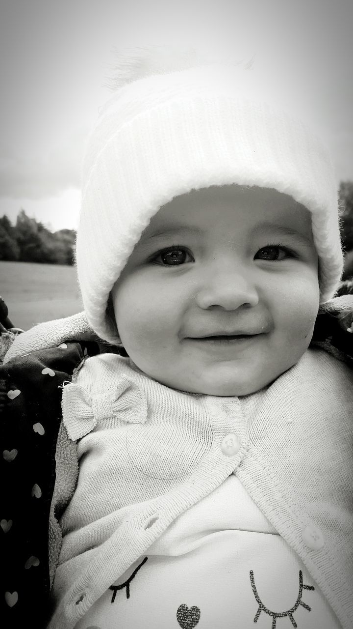 real people, childhood, cute, innocence, looking at camera, smiling, portrait, happiness, warm clothing, close-up, front view, babyhood, focus on foreground, day, outdoors, one person, lifestyles, leisure activity, nature, sky, people