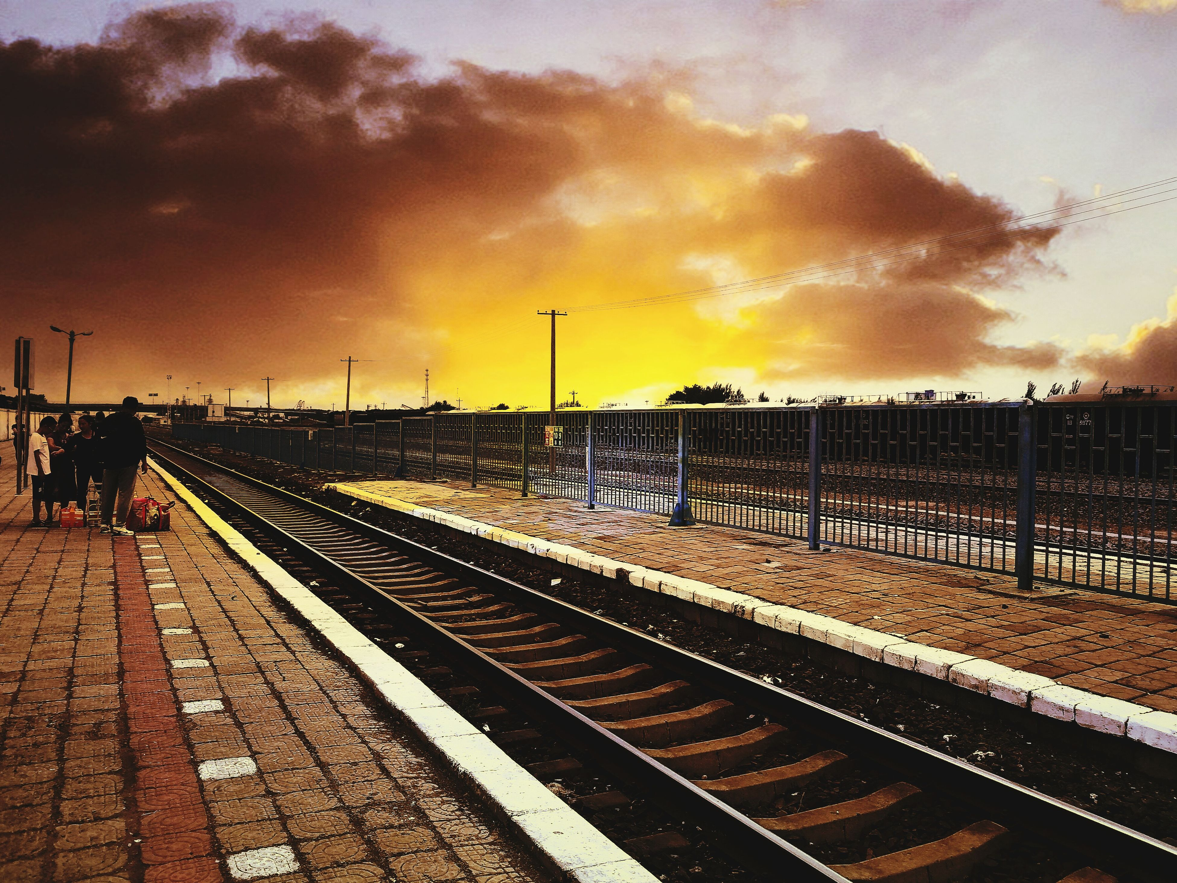 railroad track, transportation, rail transportation, sunset, sky, railroad station, cloud, cloud - sky, railroad station platform, storm cloud, diminishing perspective, long, railway track, outdoors, bright, straight, scenics, public transport, journey, the way forward, tranquil scene