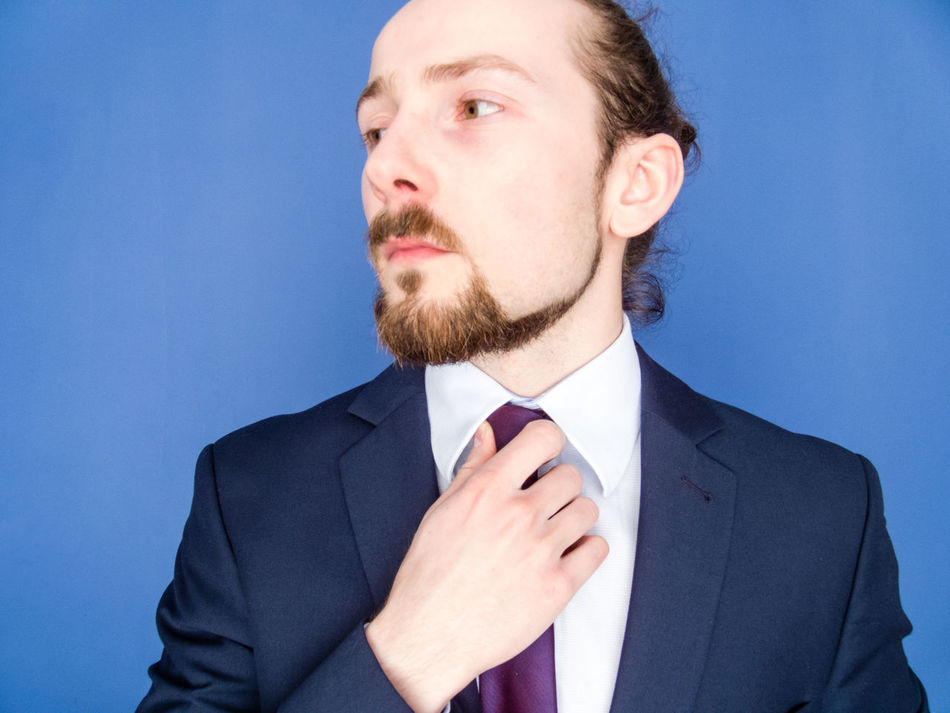 Portrait of a young handsome bearded man in a suit adjusting his tie. Success concept. Beard Blue Boss Business Businessman Confident  Manager Menswear Necktie One Person People Self Portrait Self-Confidence Standing Student Studio Shot Suit Well-dressed White Color Young Adult