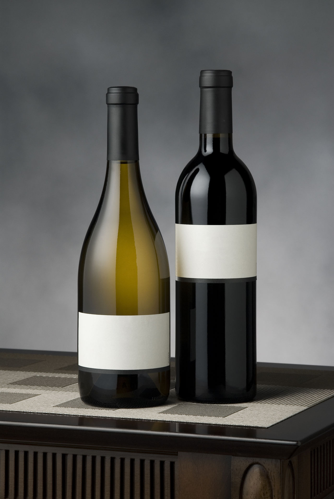 Two wine bottles Alcohol Blank Labels Cabernet_sauvignon Capsule Chardonnay Drink Elegant Labels No People No Vintage Place Mat Side By Side Still Life Studio Shot Table Top Vertical Composition Wine Wine Bottles Wines Wooden