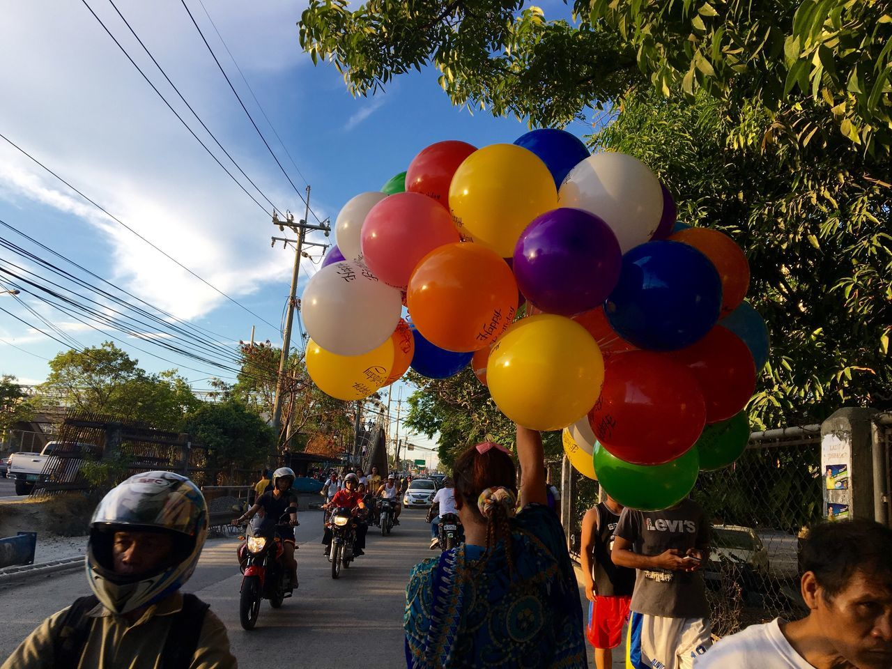 """A woman, holding """"Happy Birthday"""" balloons, walks past motorists and passers-by along a busy street in Taguig, Philippines. Balloons Happy Birthday Street Photography Motorcycles Motorcyclist Colourful Balloons Bestoftheday Color Photography Color Shapes Colour Of Life"""