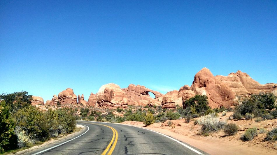 #arches #nationalpark #redrock #Utah Blue Clear Sky Copy Space Country Road Diminishing Perspective Landscape Mountain Mountain Range Nature Non-urban Scene Road Road Marking Rock - Object Rock Formation Scenics The Way Forward Tranquil Scene Tranquility Transportation Vanishing Point