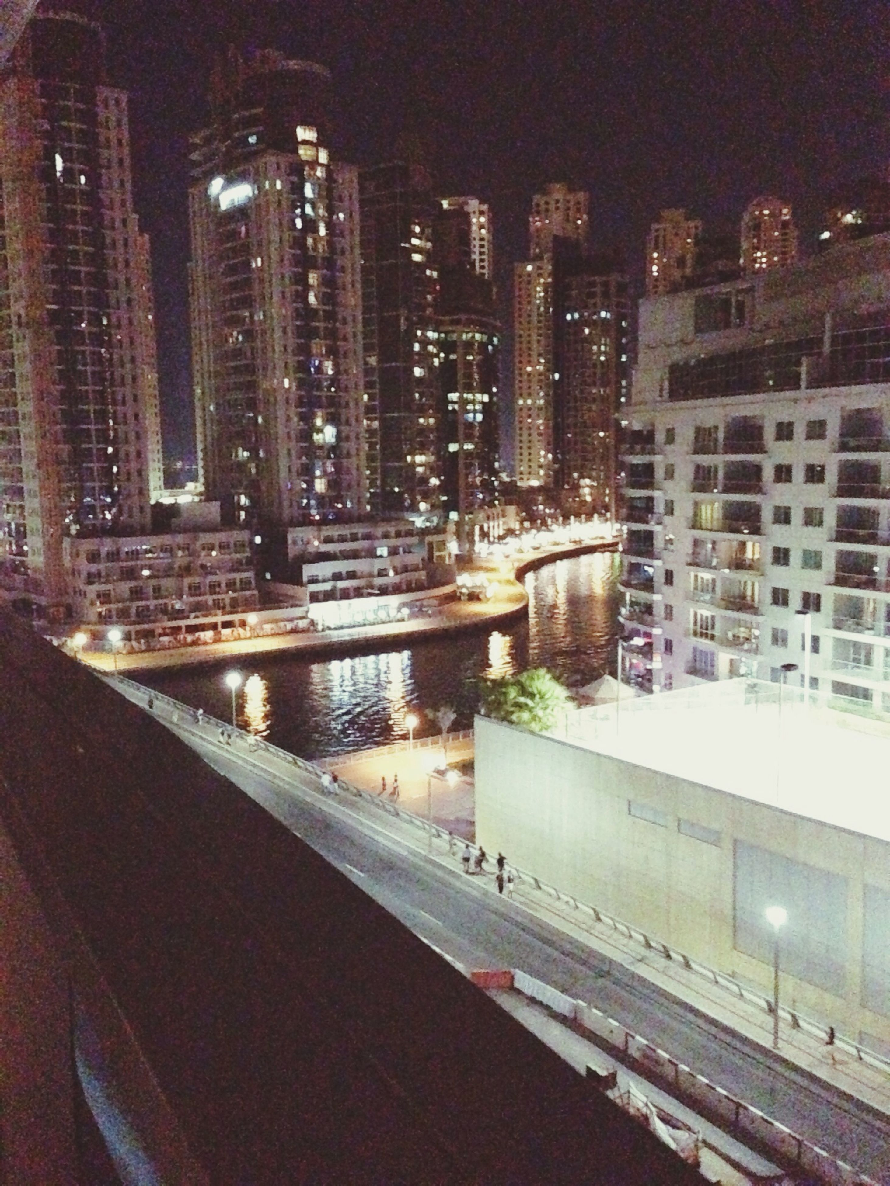 building exterior, architecture, built structure, city, night, illuminated, skyscraper, cityscape, high angle view, residential building, office building, modern, building, street, tall - high, city life, tower, residential structure, road, reflection