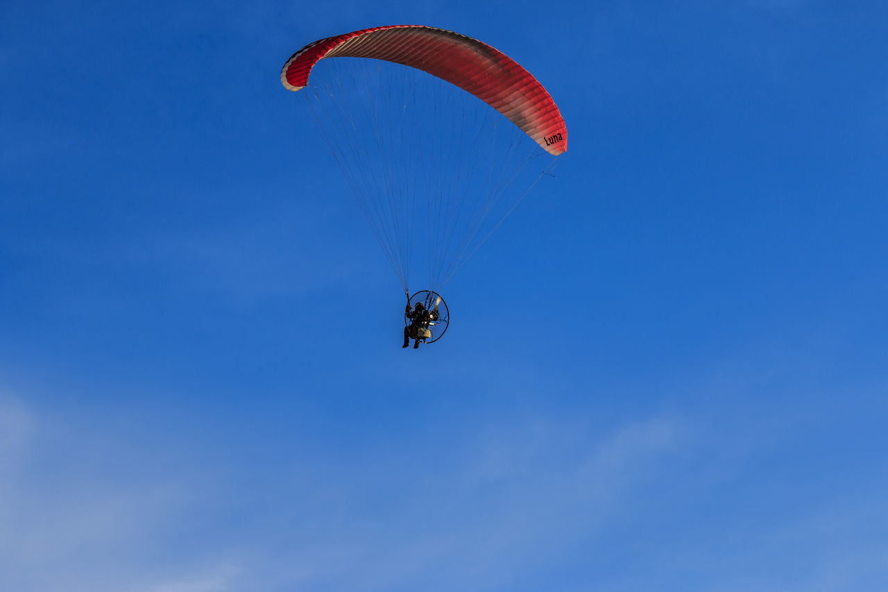 mid-air, low angle view, extreme sports, parachute, blue, adventure, day, real people, leisure activity, outdoors, flying, lifestyles, one person, nature, sport, sky, paragliding, people