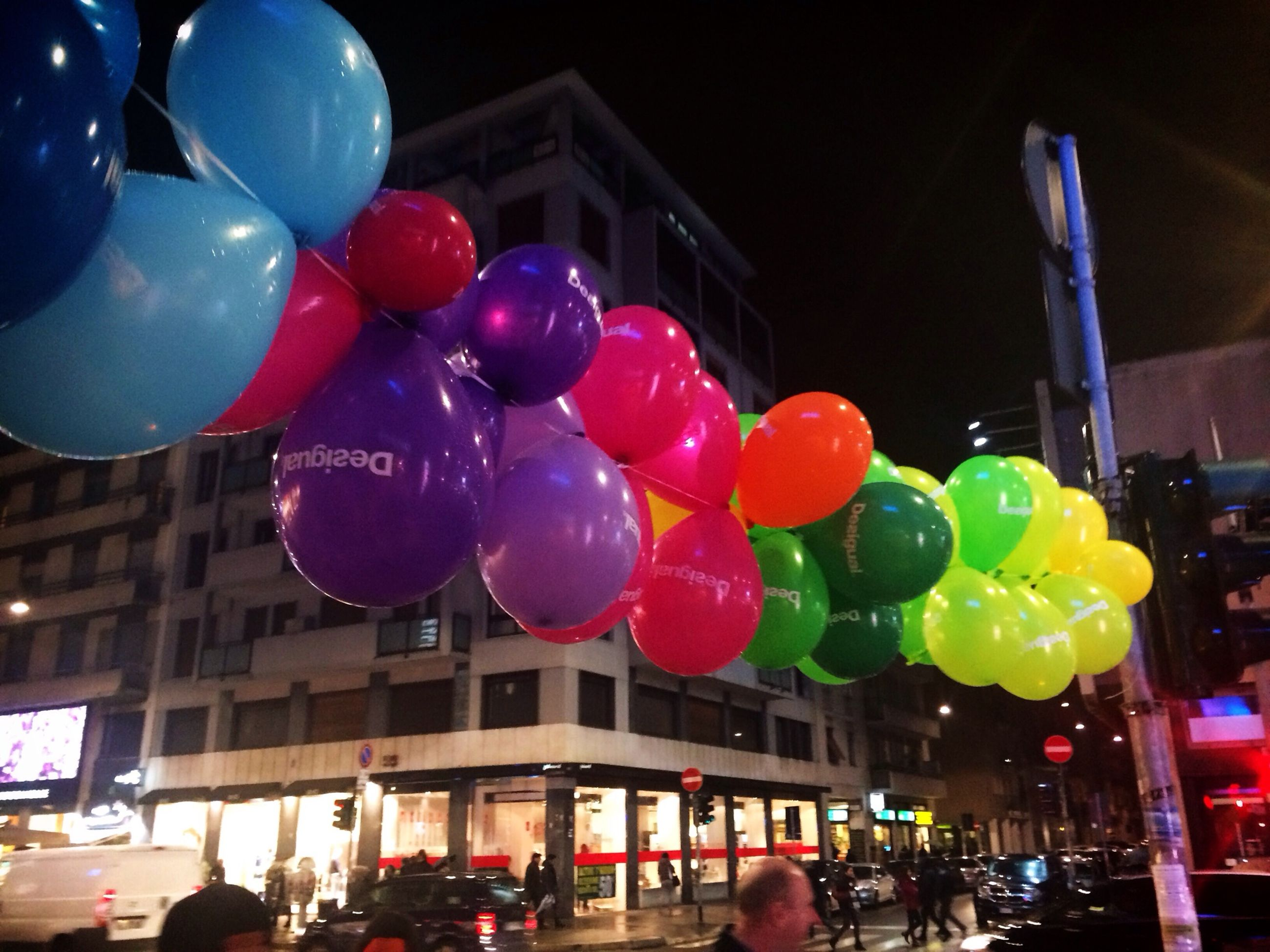 multi colored, balloon, celebration, illuminated, building exterior, hanging, night, built structure, architecture, variation, city, decoration, lighting equipment, large group of objects, choice, low angle view, colorful, leisure activity, outdoors