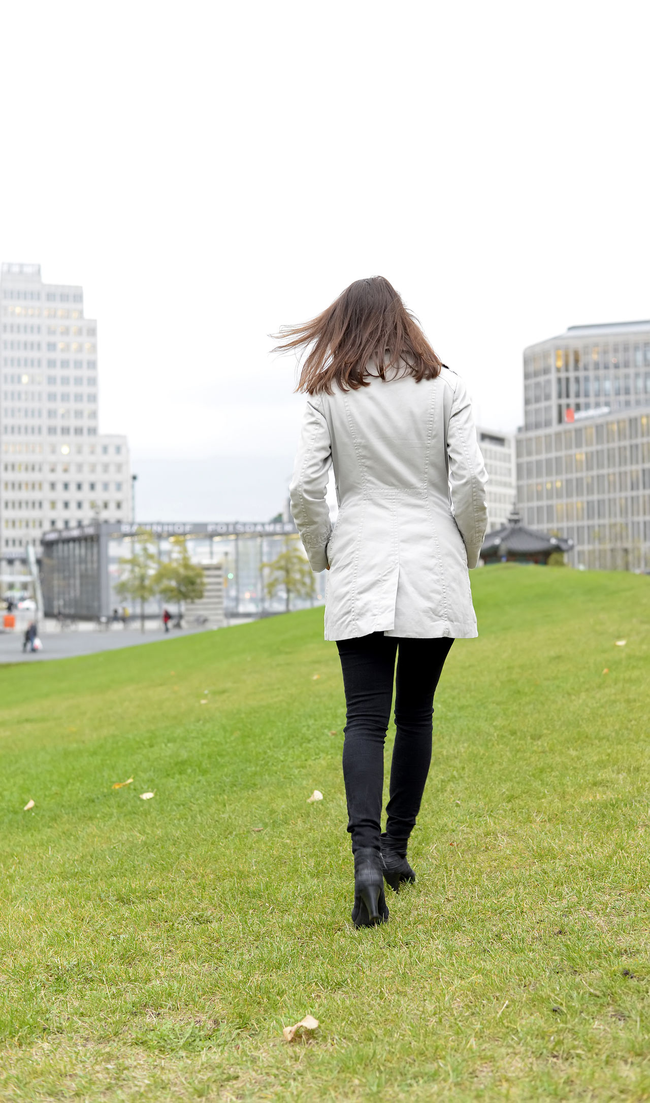 businesswoman in the city, rear view Architecture Business Businesswoman City Cityscape Coat Contemplating Full Length Green Hurry Livestyle Manager Meadow One Person Outdoors Pensive Rear View Sky Slim Stress Strolling Thinking Urban Walking Woman