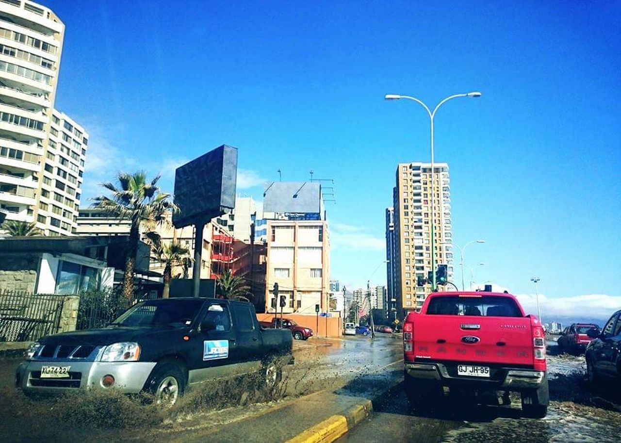 car, land vehicle, transportation, architecture, city, building exterior, road, skyscraper, sky, blue, outdoors, day, no people, modern