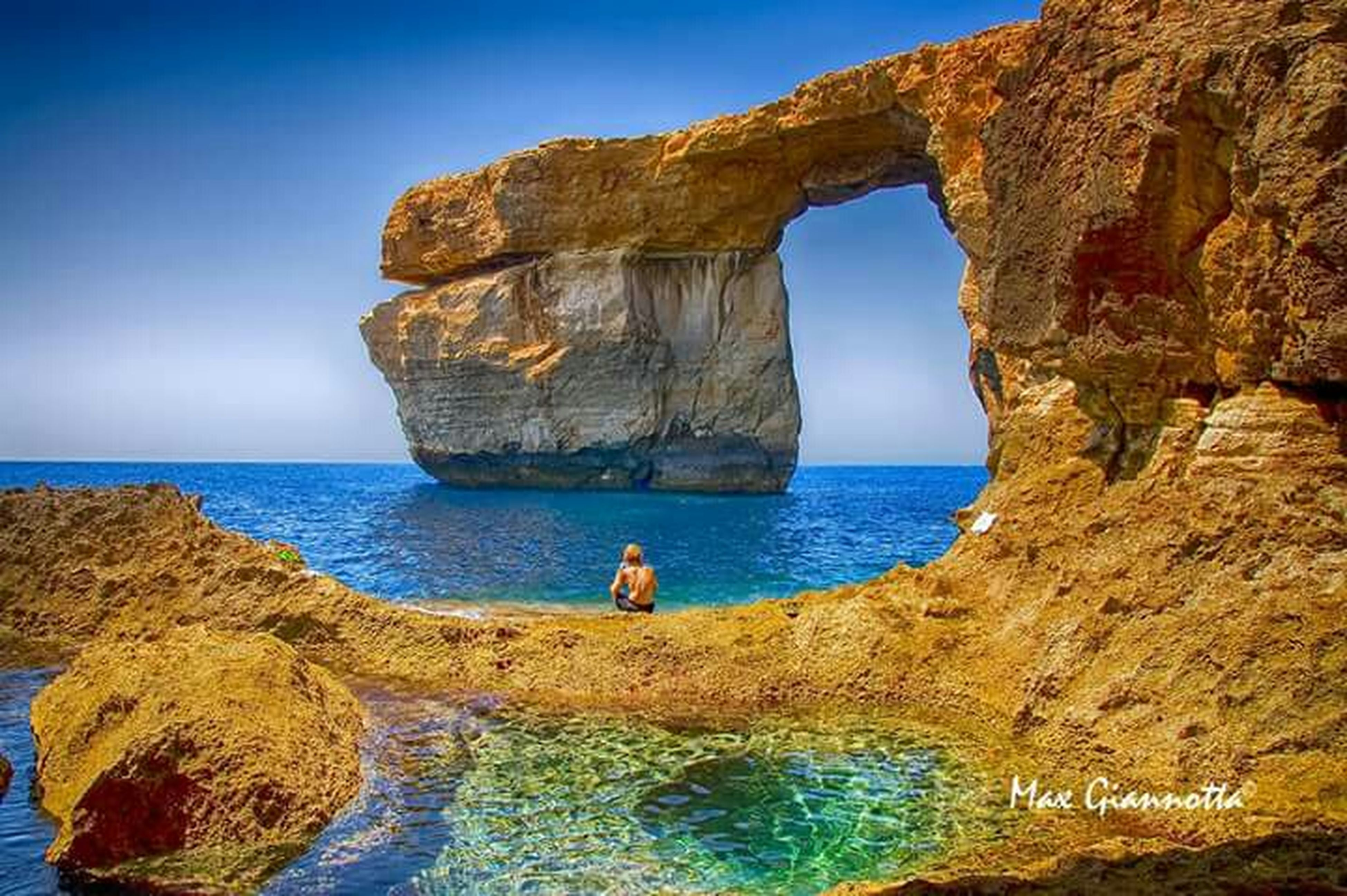 sea, water, horizon over water, blue, rock - object, rock formation, tranquility, clear sky, cliff, scenics, rock, tranquil scene, sky, nature, beauty in nature, sunlight, day, lifestyles
